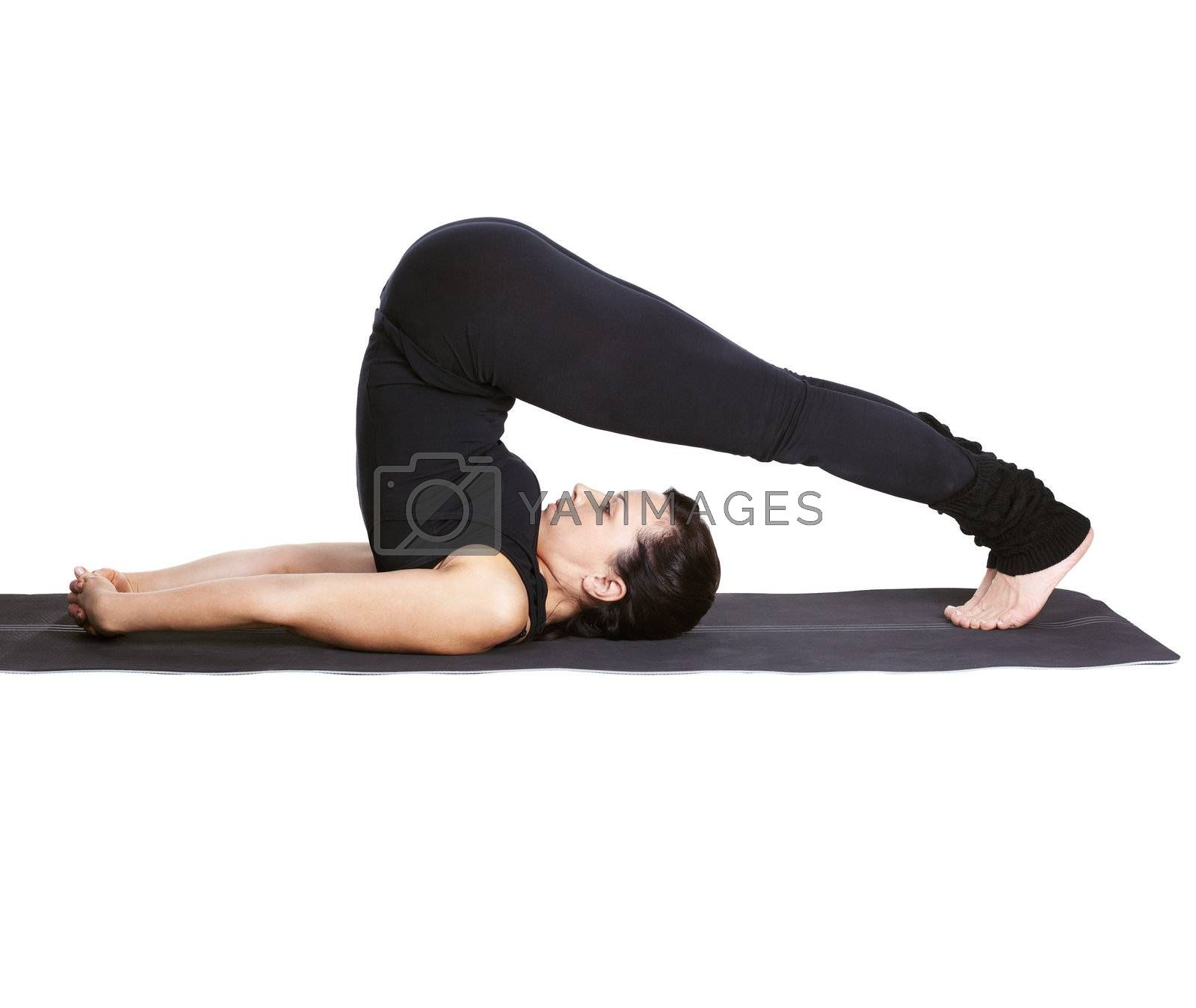 full-length portrait of beautiful woman working out yoga exercise halasana (plough pose) on fitness mat