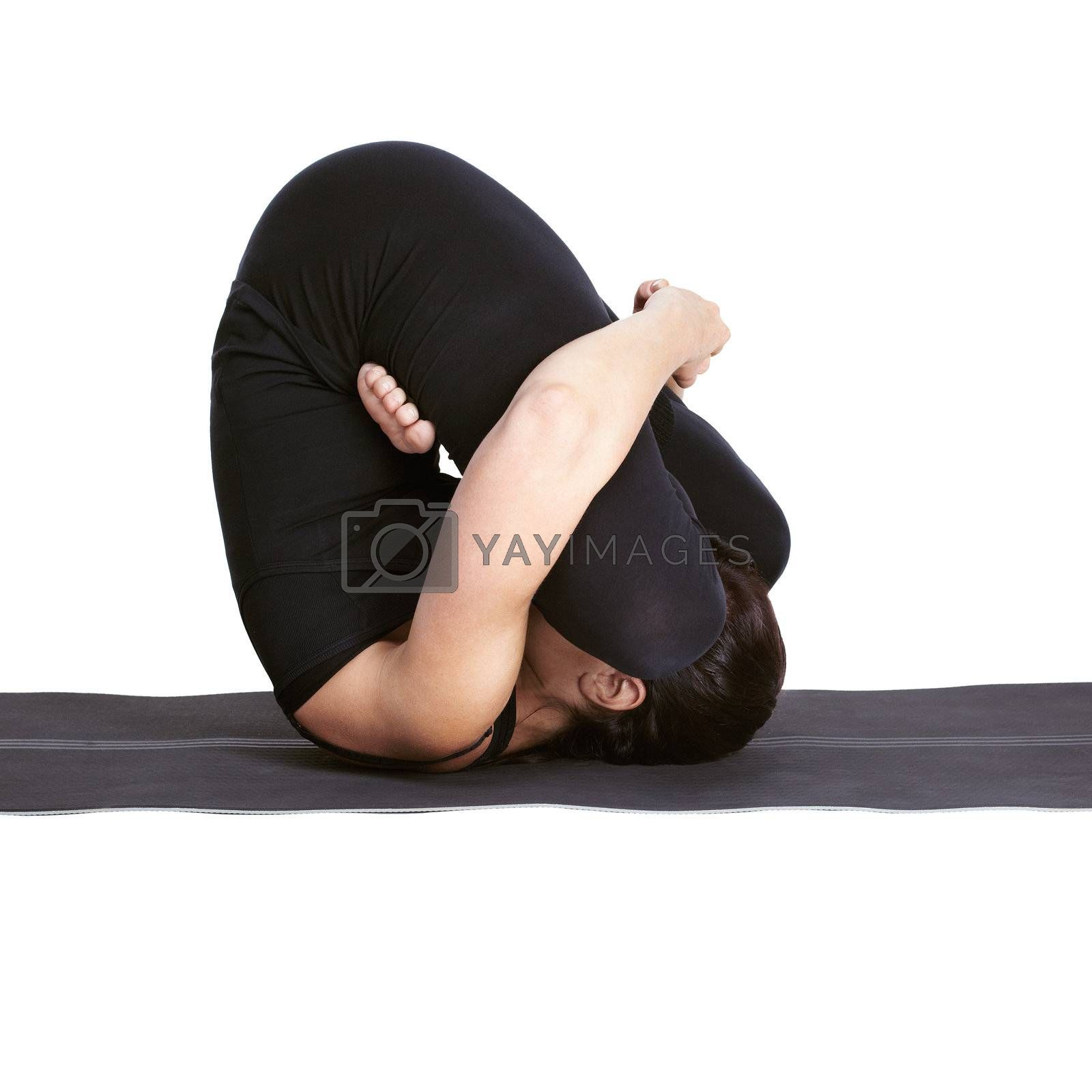 full-length portrait of beautiful woman working out yoga exercises pindasana pose on fitness mat