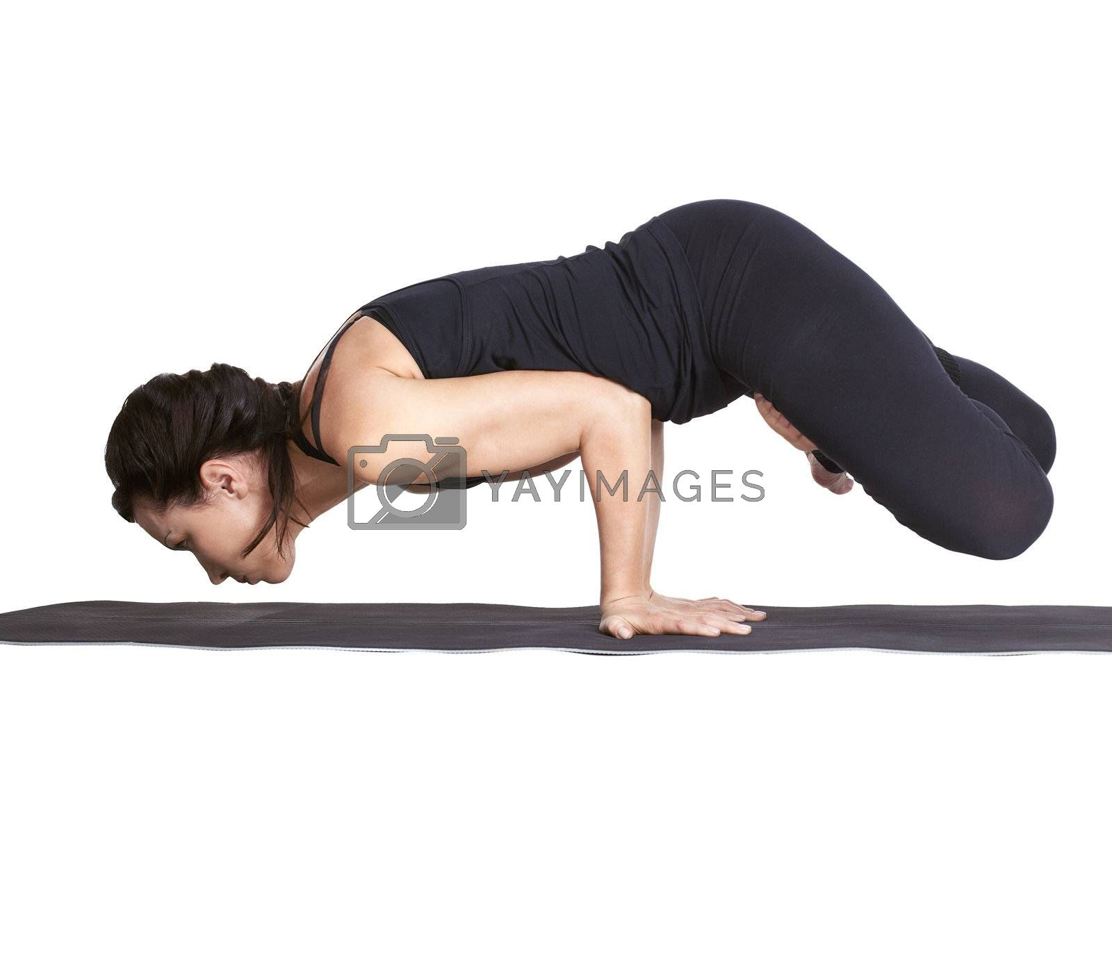 full-length portrait of beautiful woman working out yoga exercise balancing on hands in padma mayurasana pose