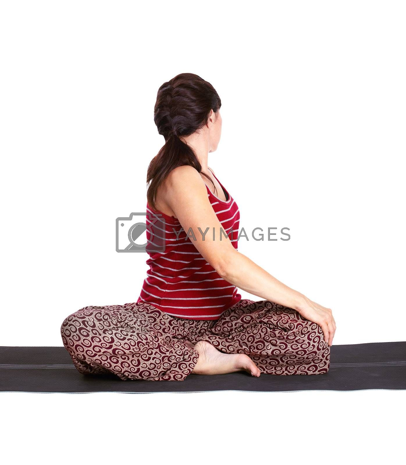 full-length portrait of beautiful woman working out yoga twisting exercise on fitness mat