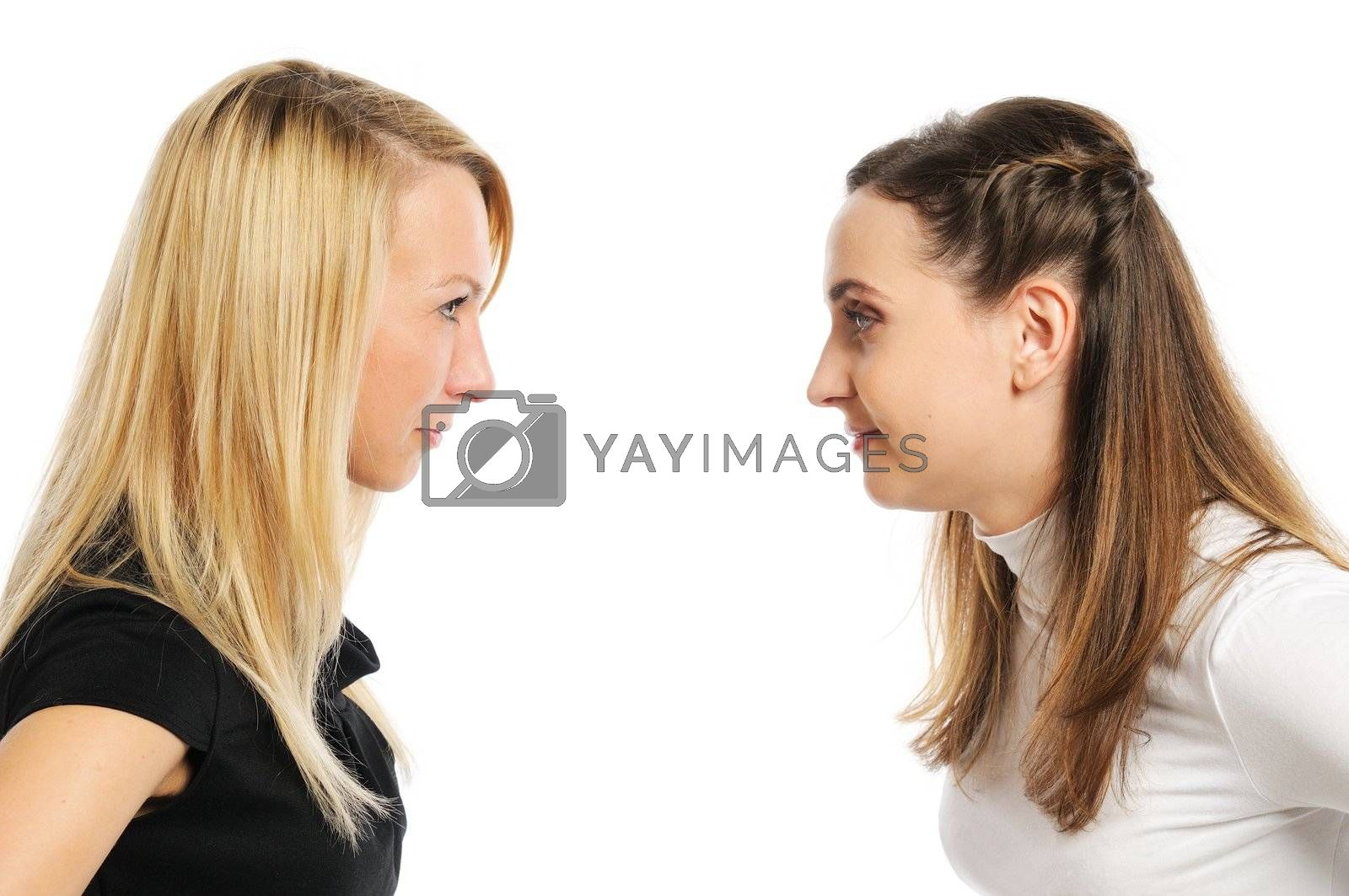 Two attractive women attentively look at each other. Isolated on white.