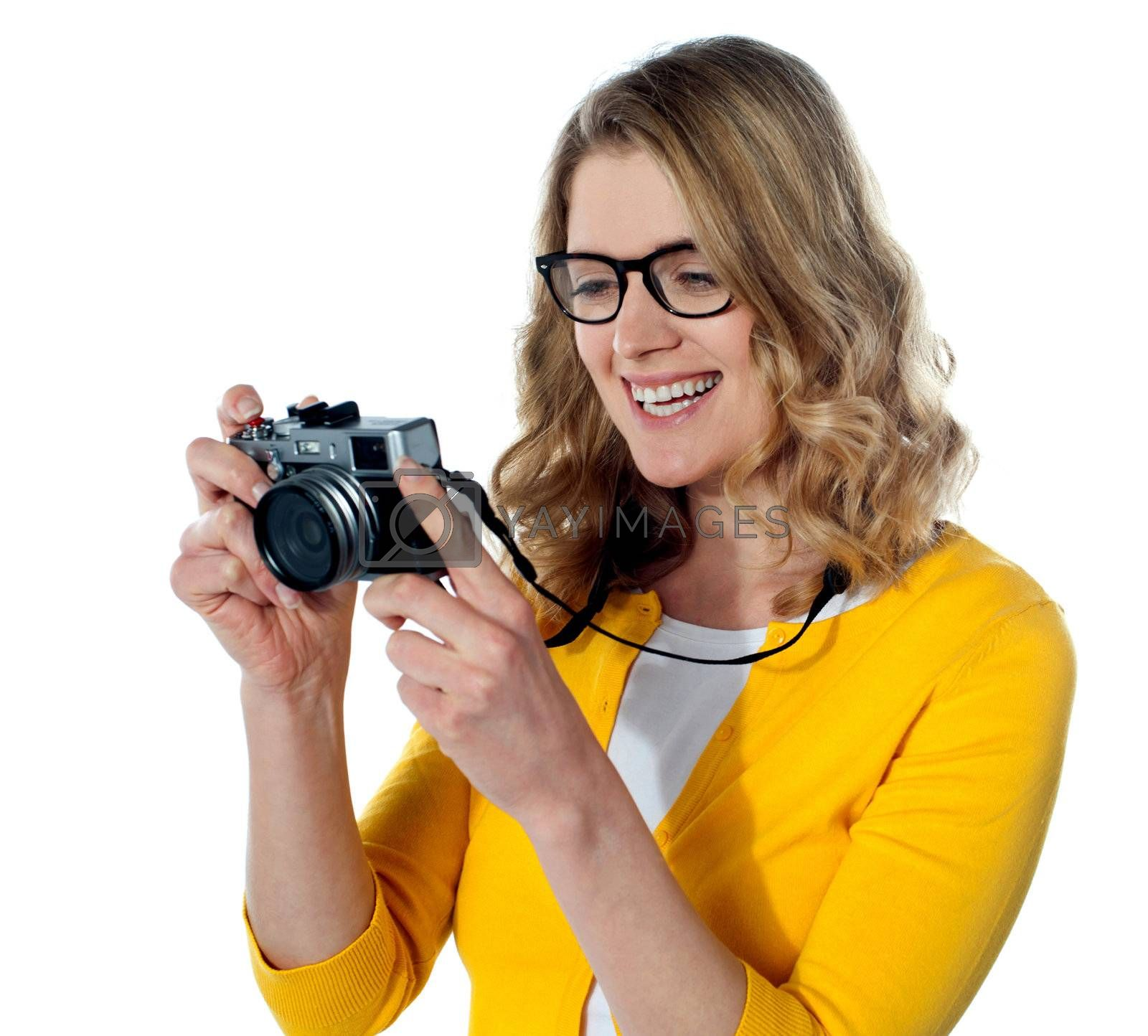 Smiling caucasian photographer looking at her camera