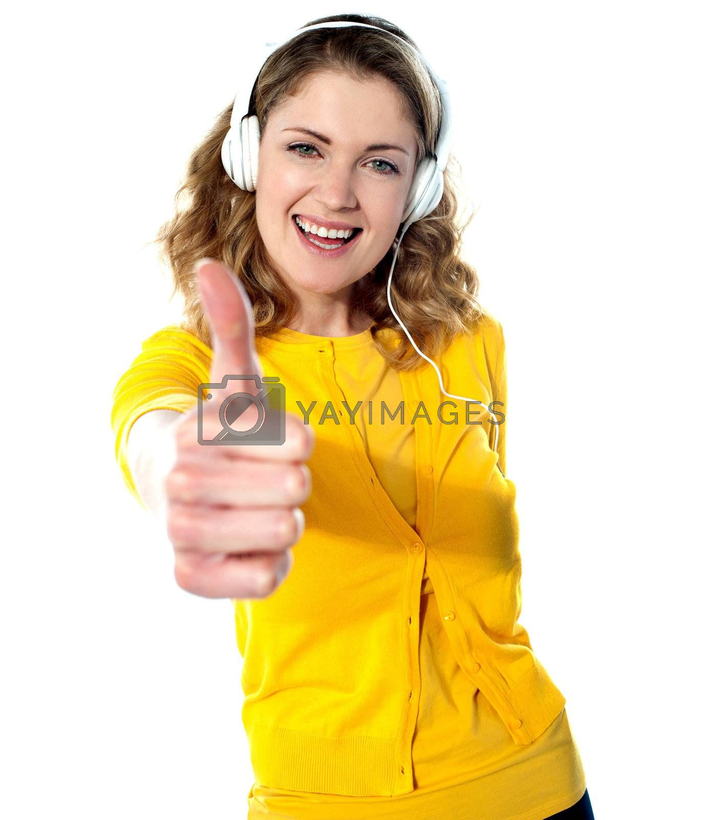 Thumbs-up woman enjoying music on her mp3 player