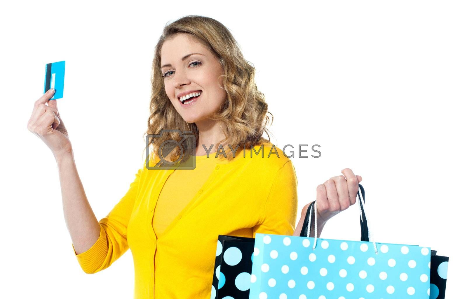 Attractive woman holding cerdit-card with shopping bags smiling against white background