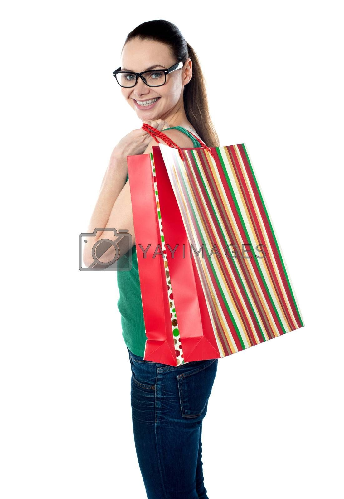 Side view of woman holding shopping bags against white background