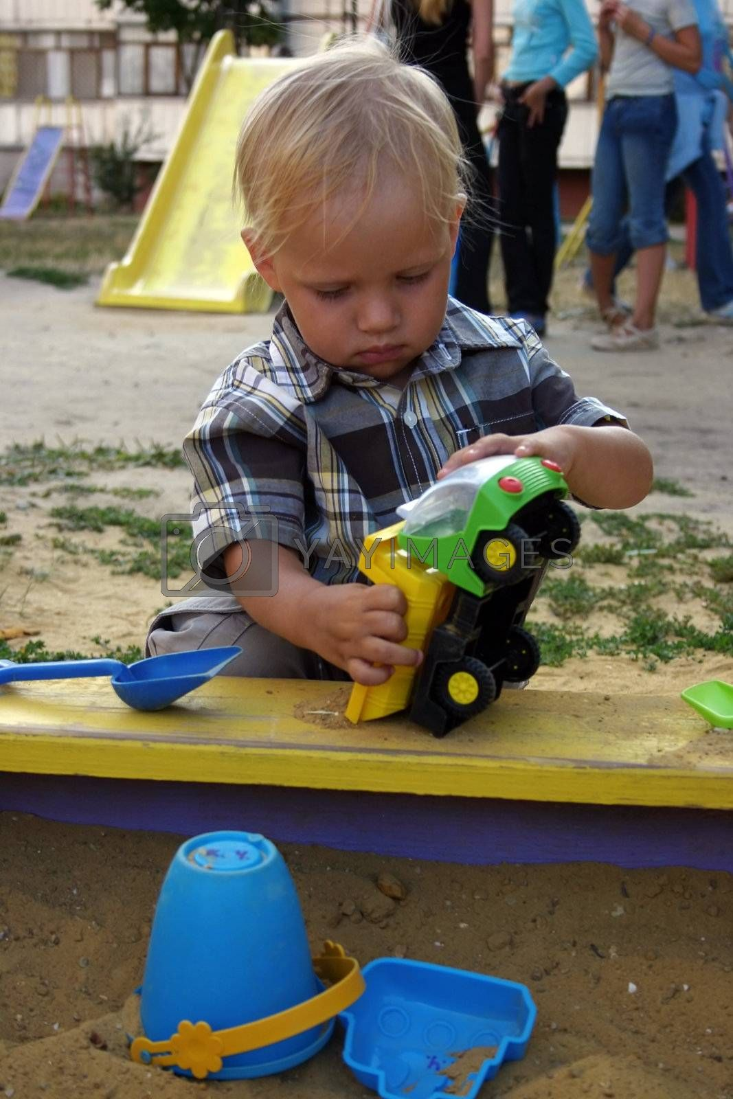 baby boy playing with toy auto in sand box