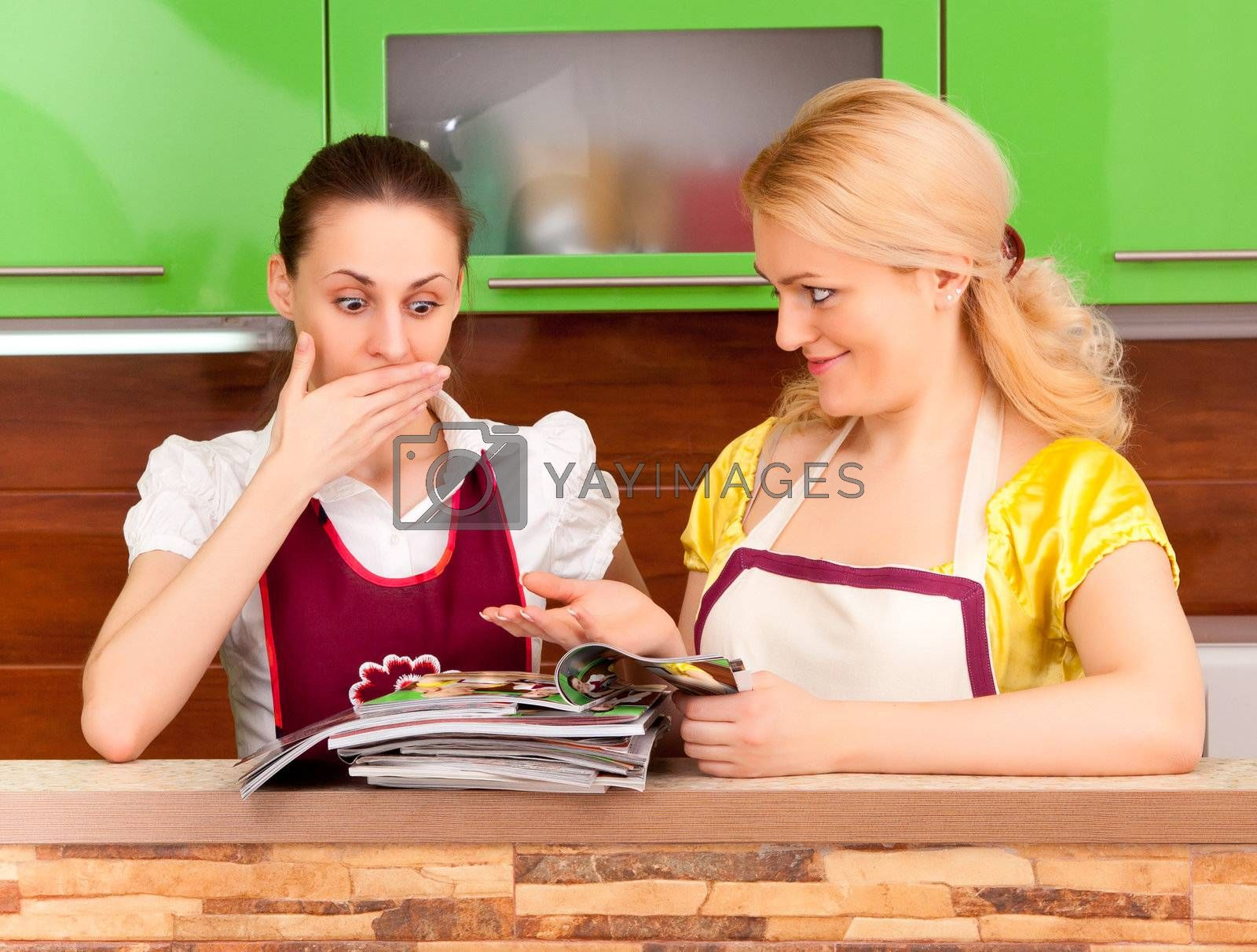 Two young women discuss fashion magazines in the kitchen