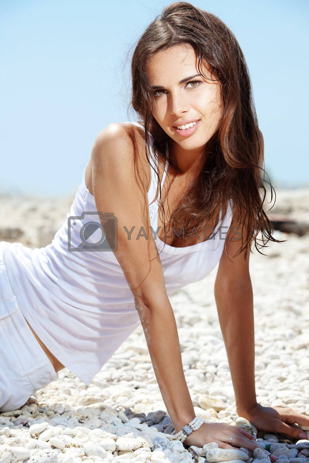Portrait of beautiful young woman with golden tan resting at beach in summer