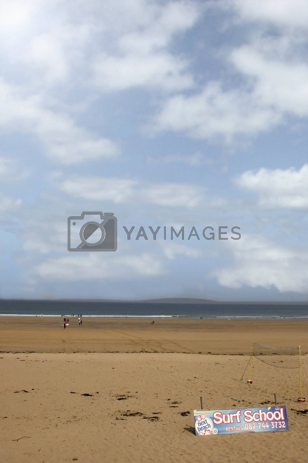 sandy beach with children getting ready to be taught surfing in ballybunion county Kerry Ireland in black and white