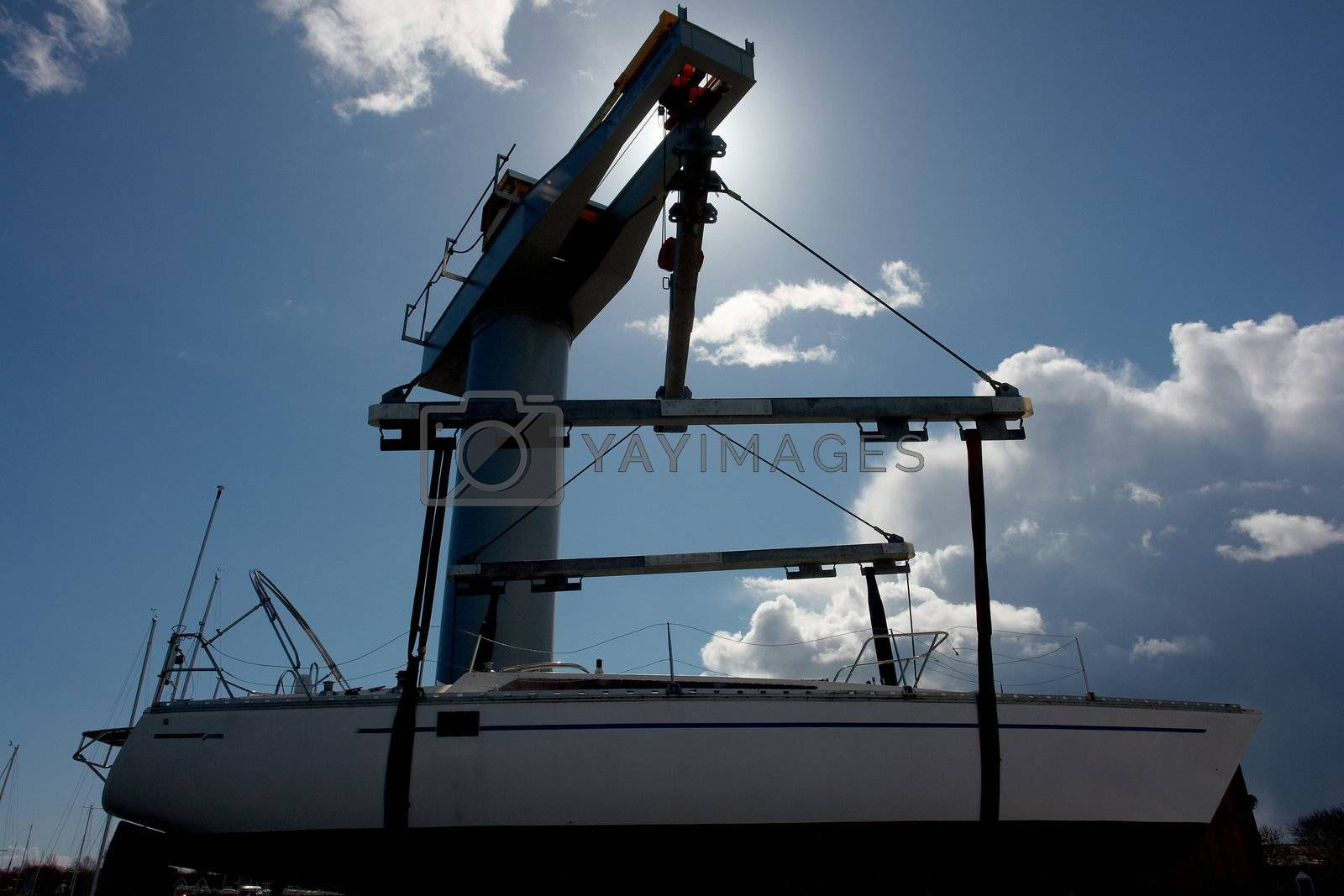 Sailboat lift up by a heavy industrial boat lifter for maintenance