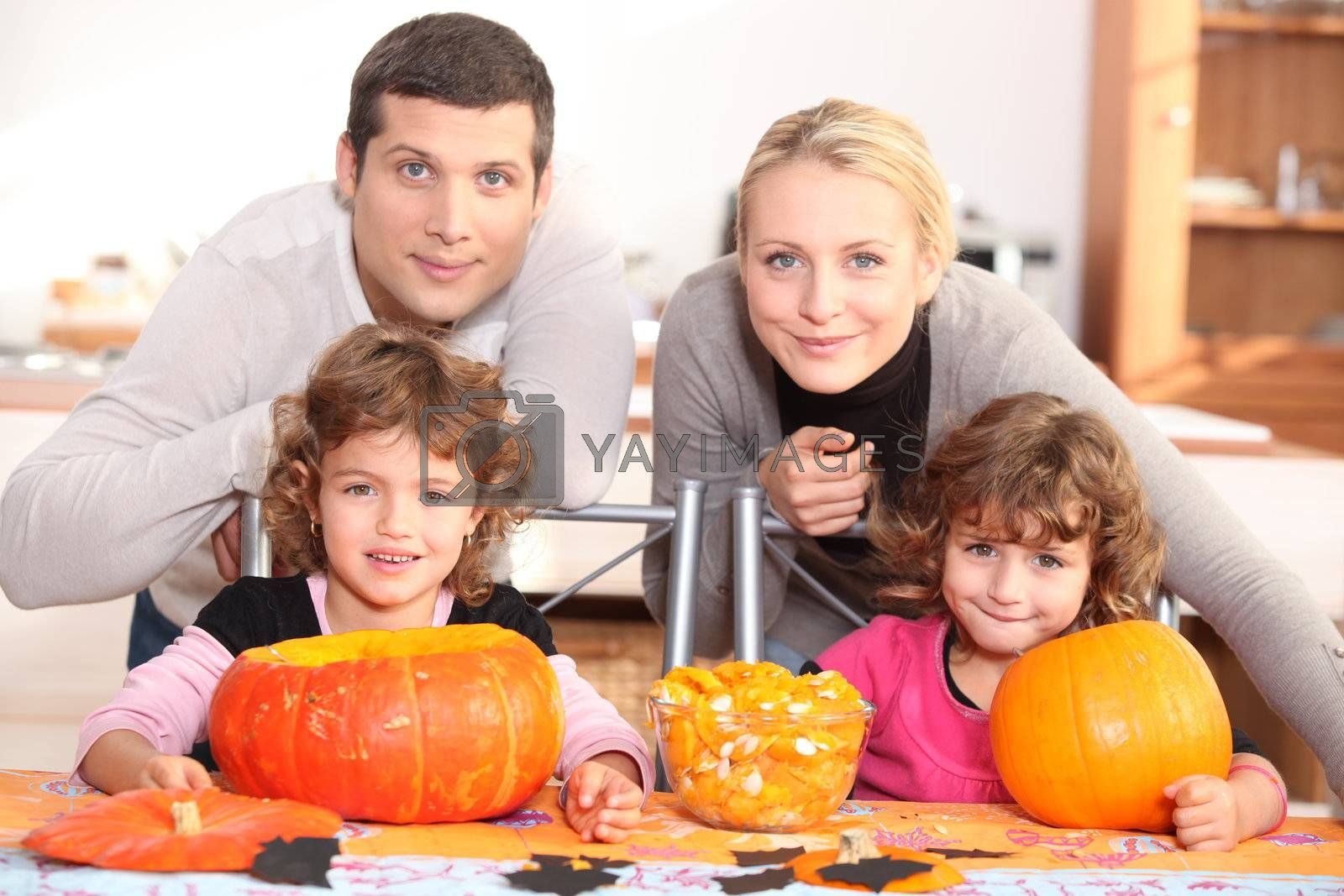 A family carving Halloween pumpkins. by phovoir