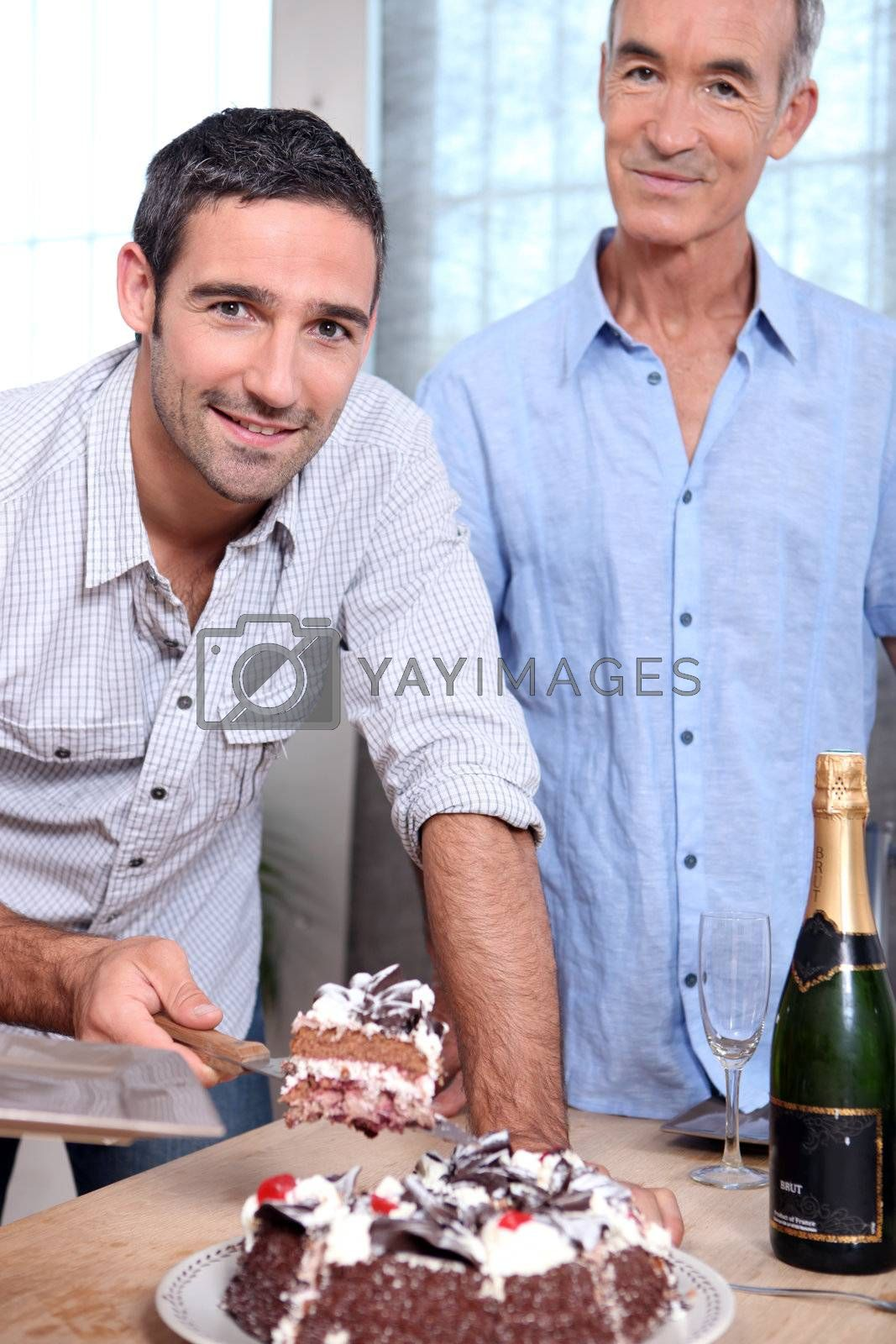 Two men cutting celebration cake by phovoir