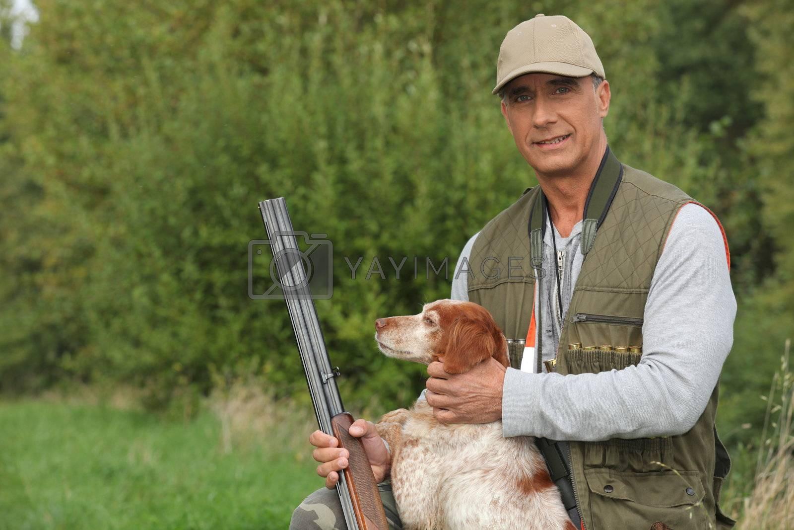 Hunter crouching by dog