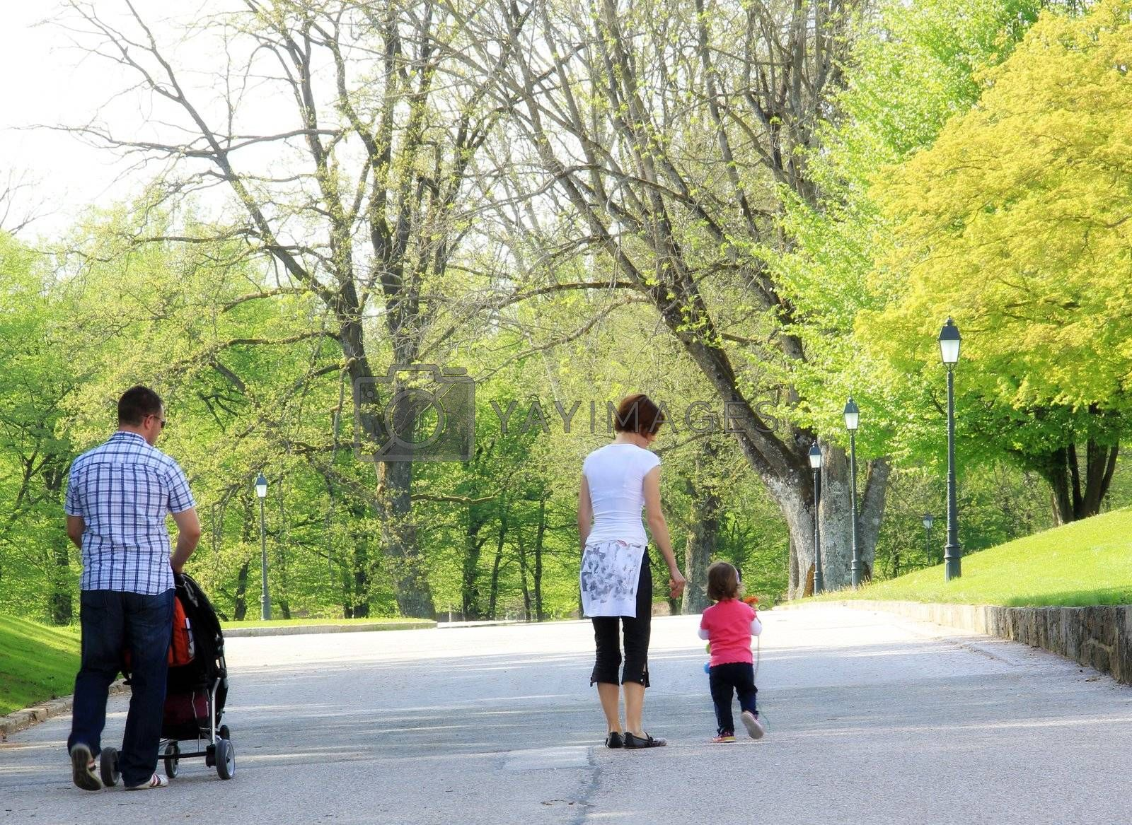 Young and happy family having fun in the park, relaxing, enjoying in beautiful early spring nature.