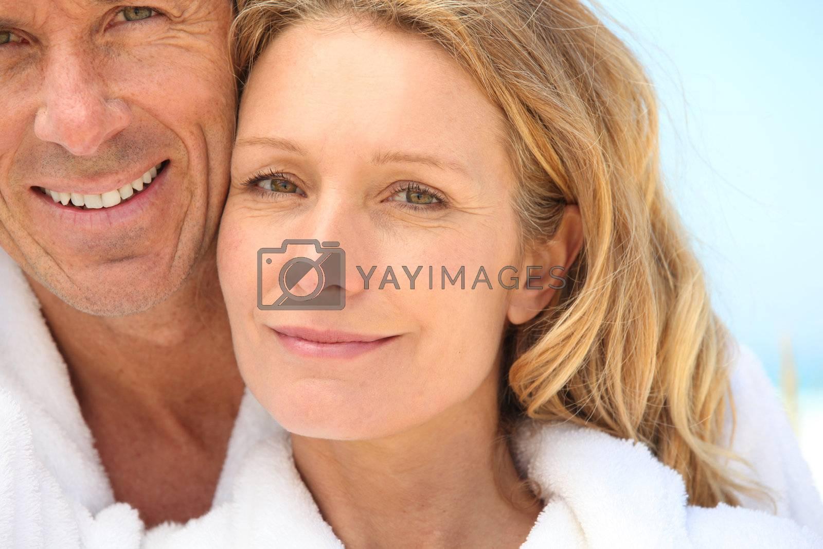 Couple wearing bath robes stood outside