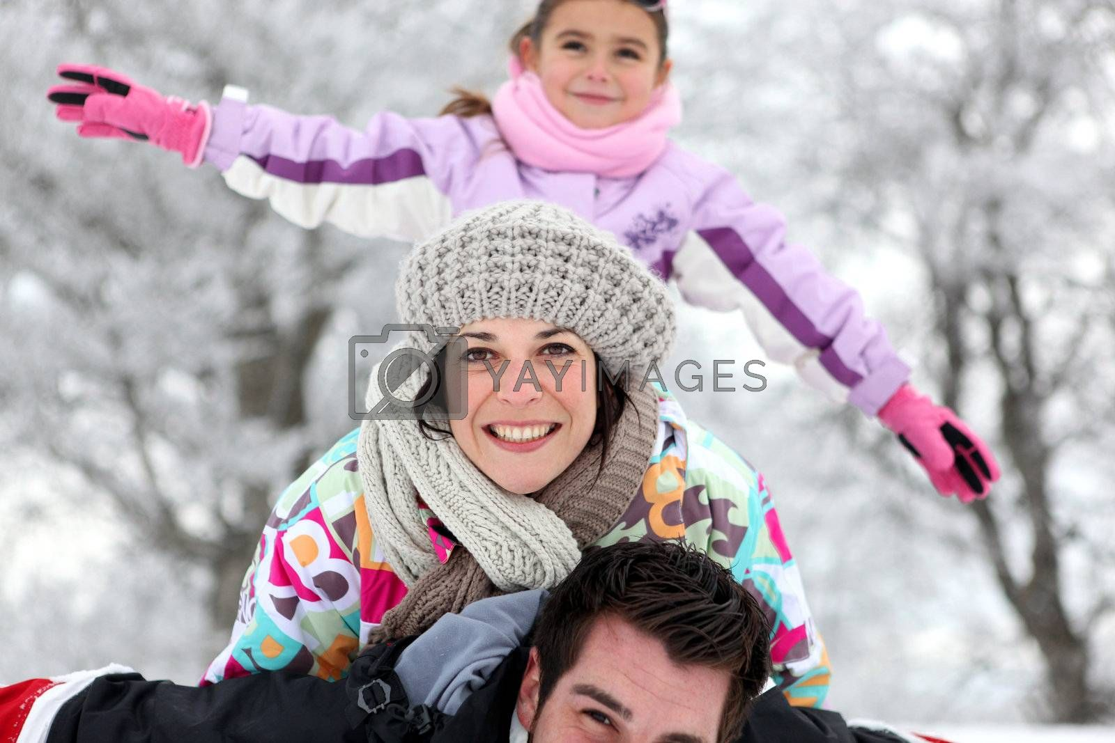 Family having fun outdoors on a cold winter's day by phovoir