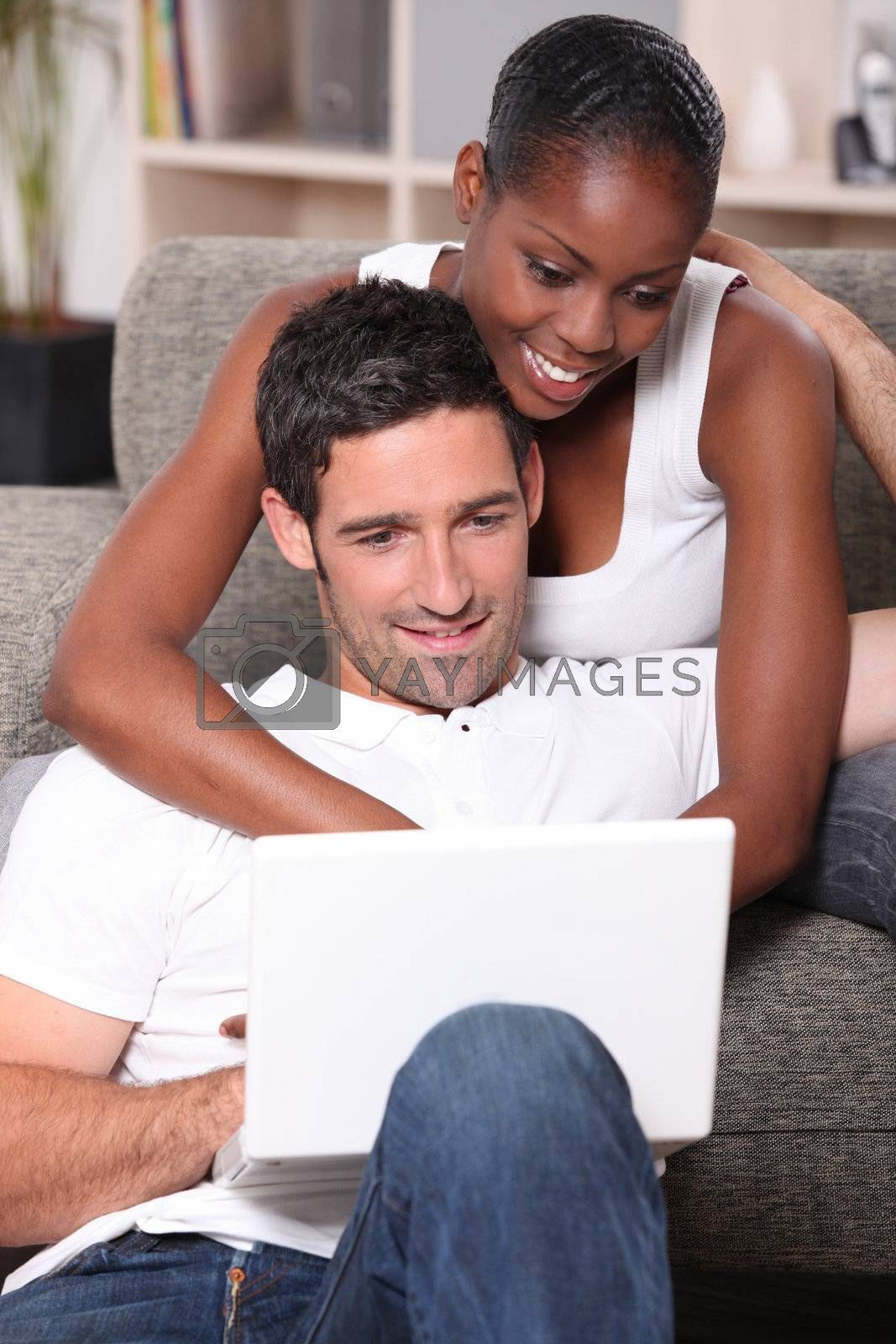 black woman is cuddling her boyfriend and doing computer by phovoir