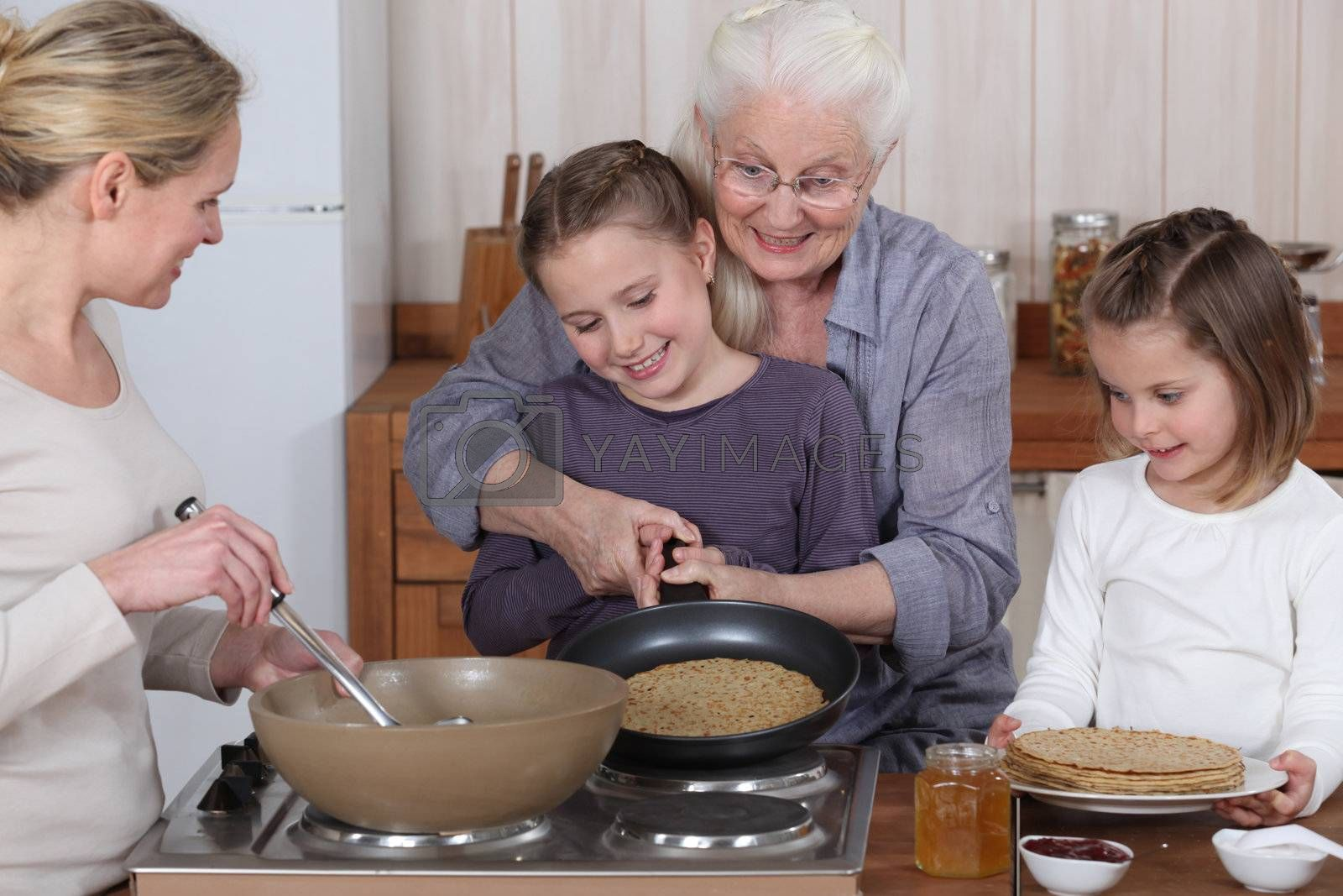 Family cooking pancakes by phovoir