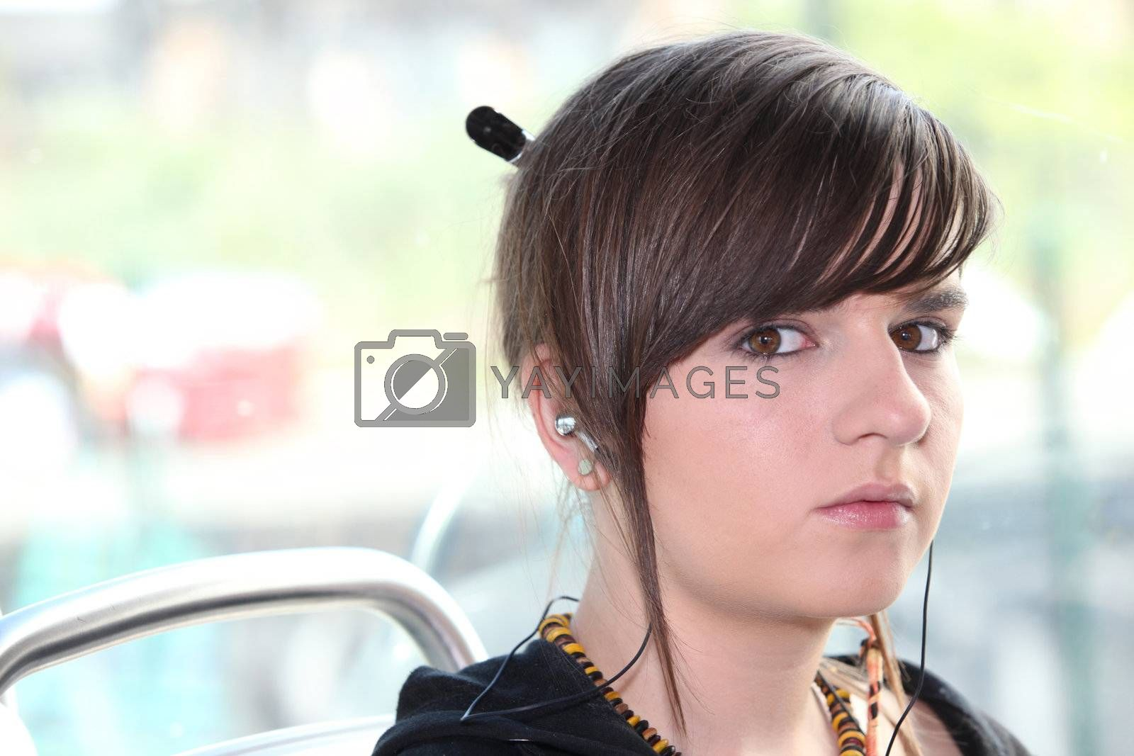 Closeup of girl with earphones sitting on a tram by phovoir