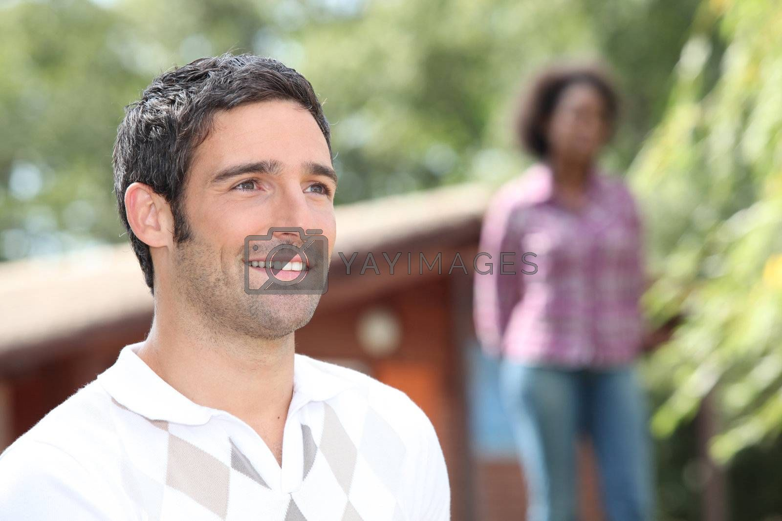 Man standing outside a log cabin with a woman out of focus in the background
