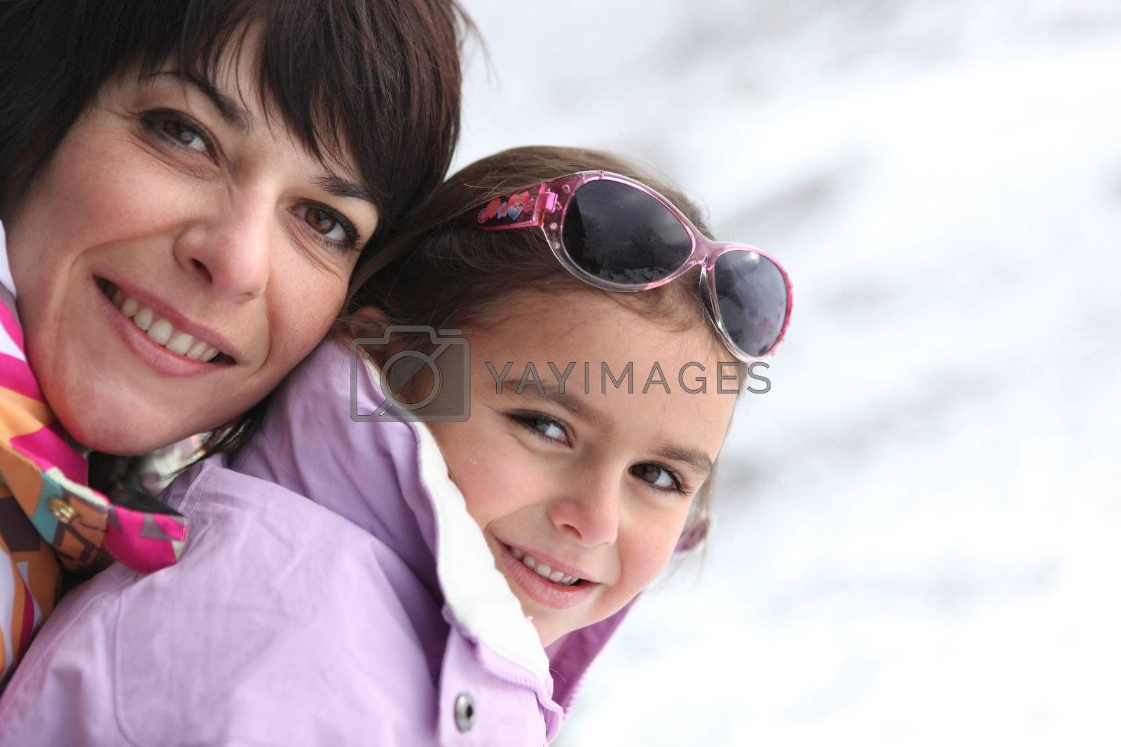 Mother and daughter playing in the snow by phovoir
