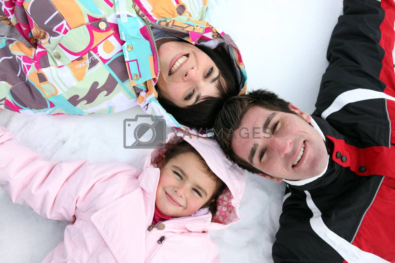 Family laying in the snow by phovoir
