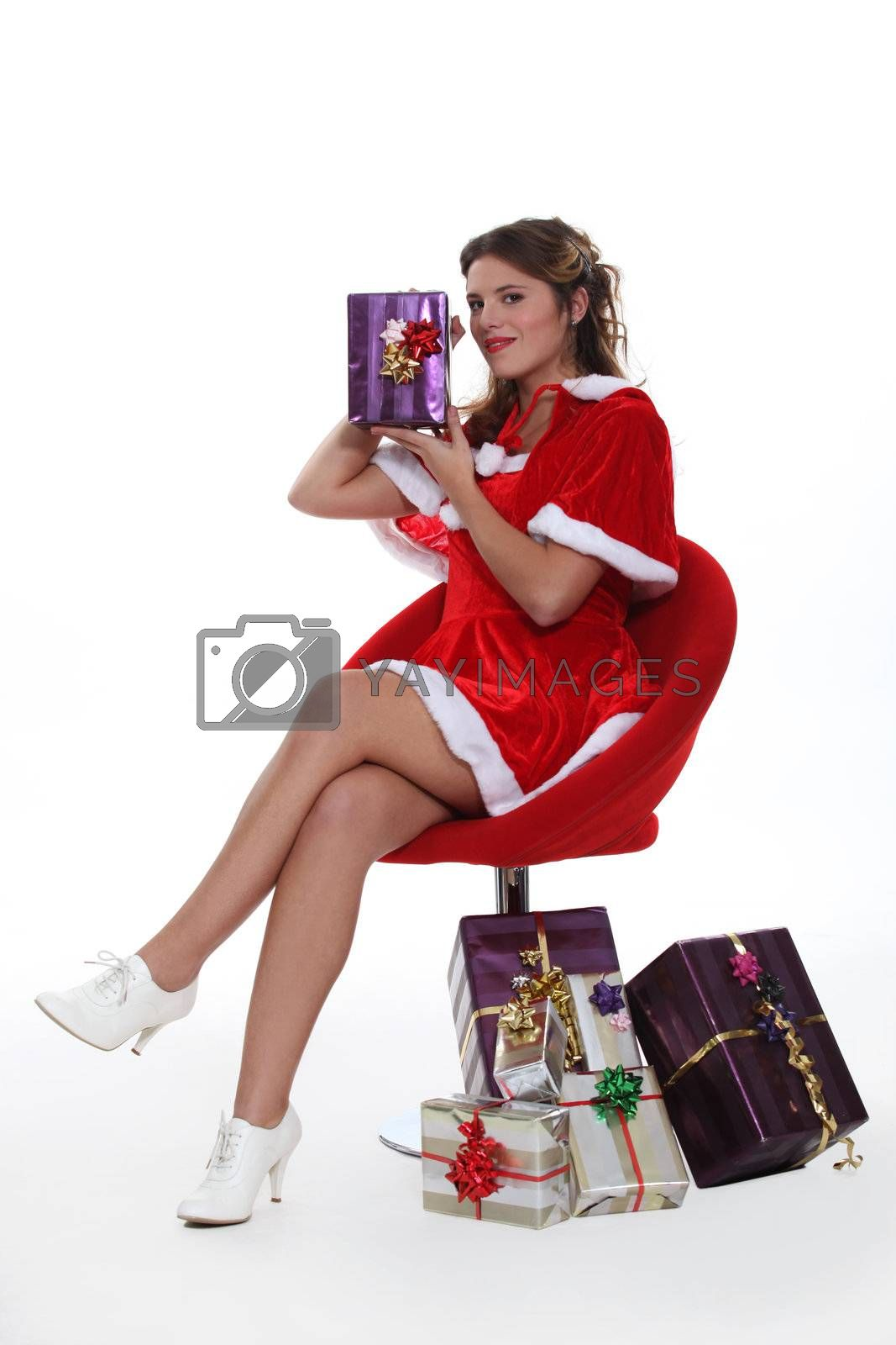 Woman dressed as Mrs. Claus holding a present