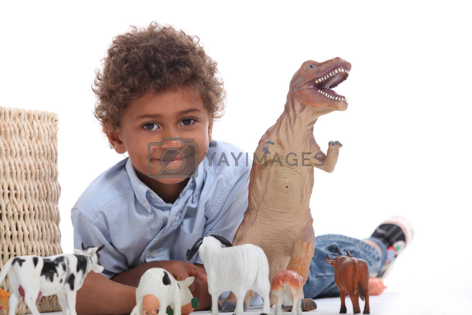 Young boy playing with a toy dinosaur and collection of domestic animals
