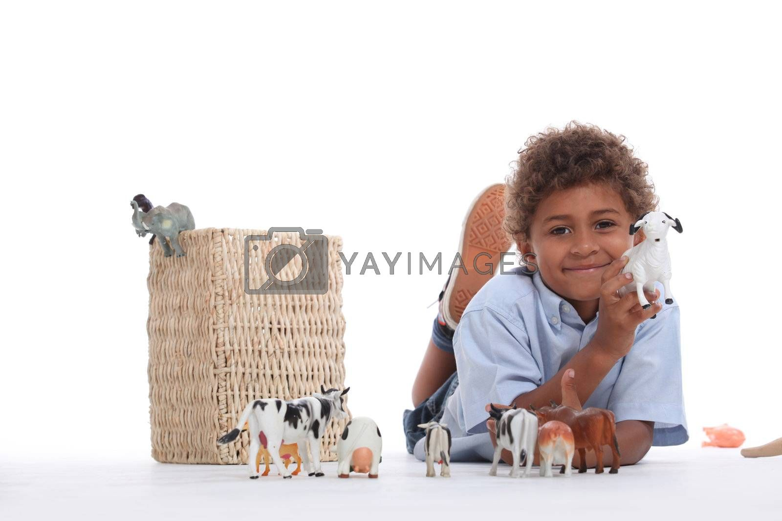 Little boy playing with plastic toy animals
