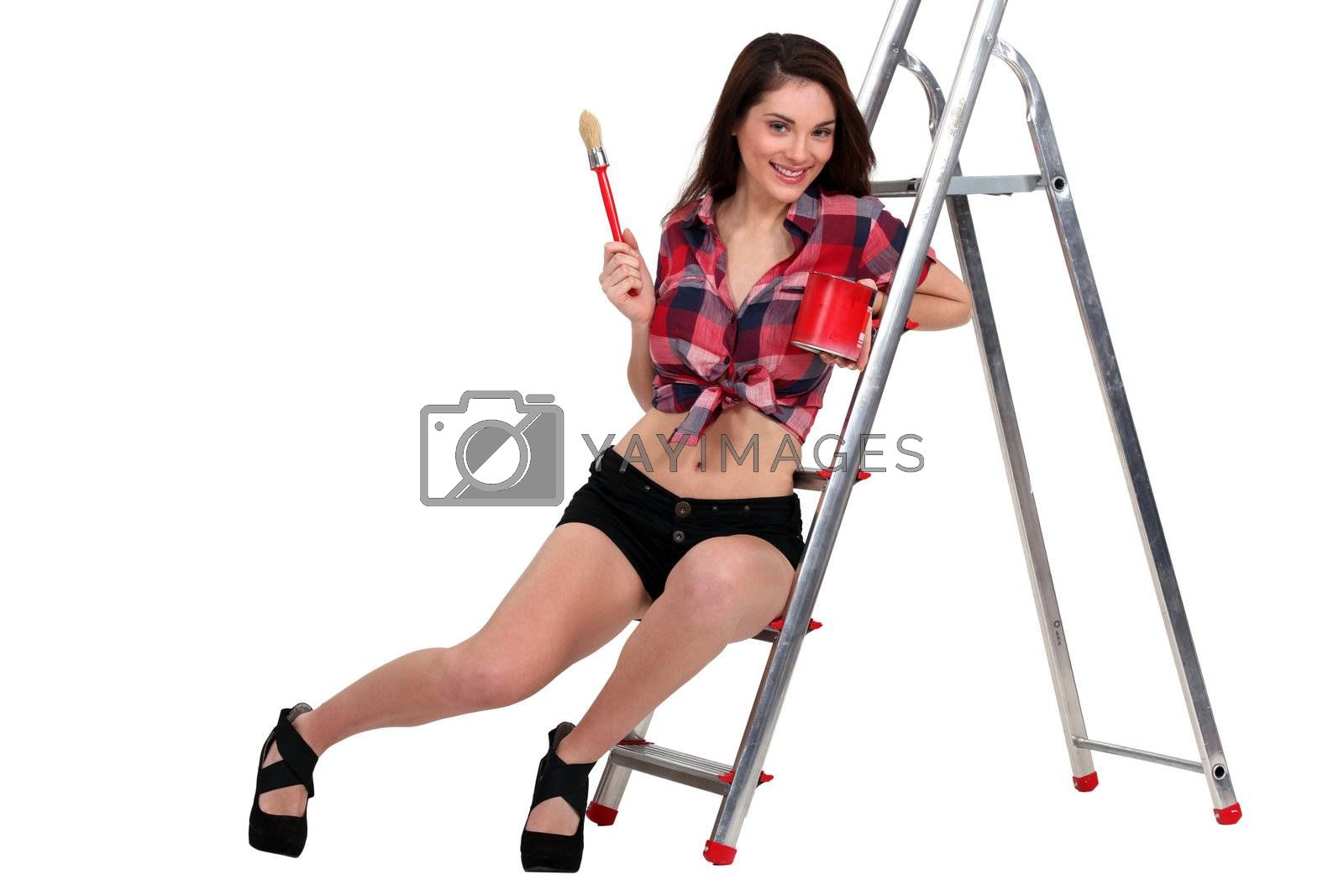 Sexy woman sat on ladder holding paint pot Royalty Free