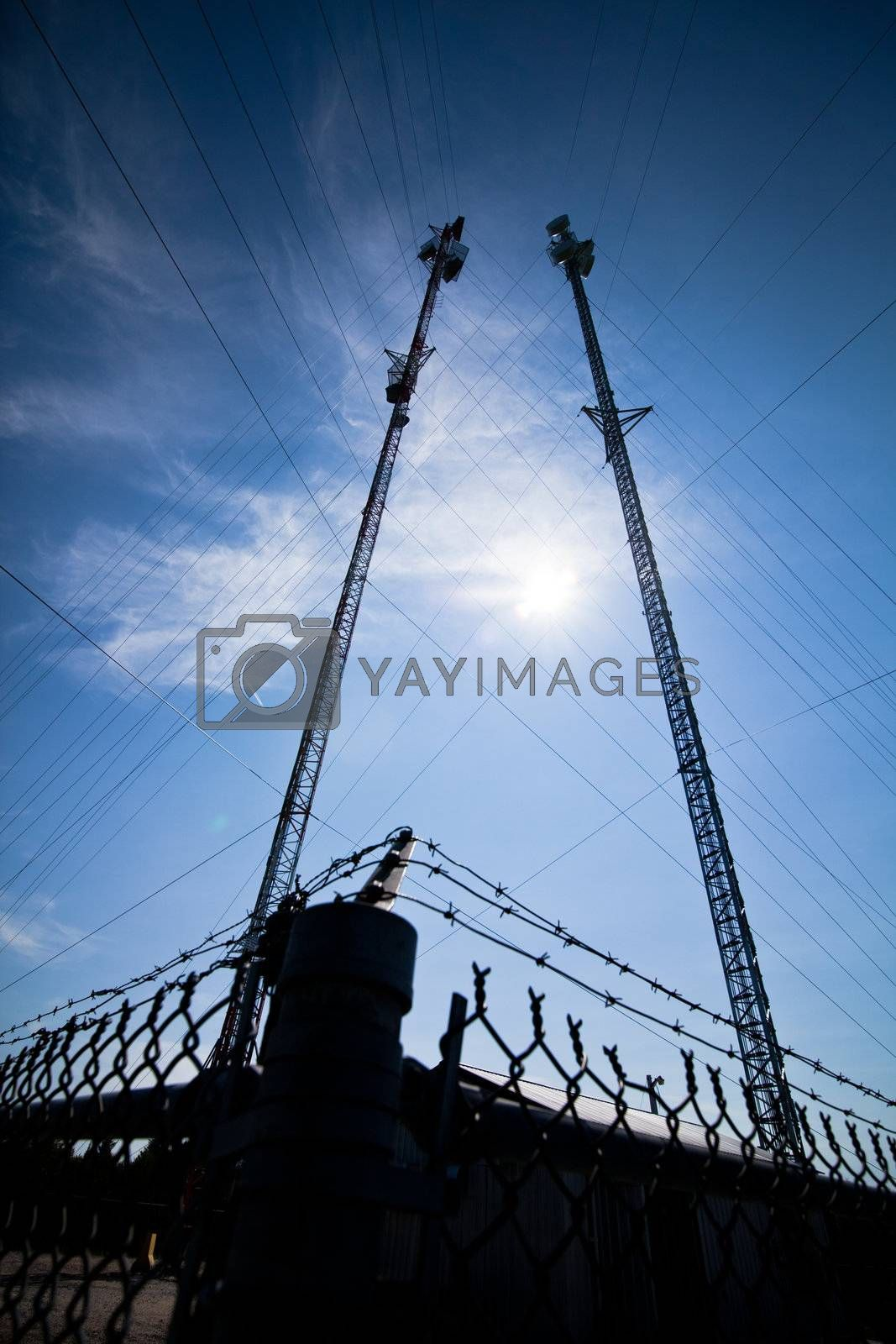 Pole with electrical wires and communication tower surounded by a fence