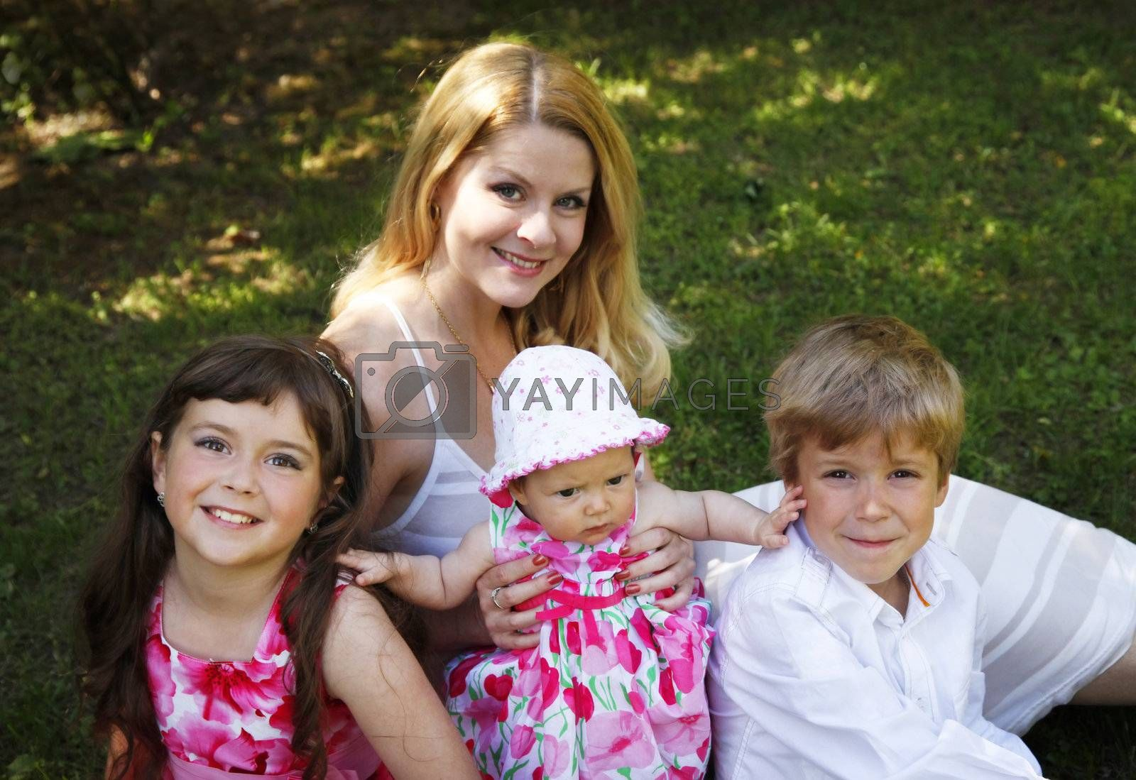Portrait of beautiful happy smiling mother with children outdoor, on nature