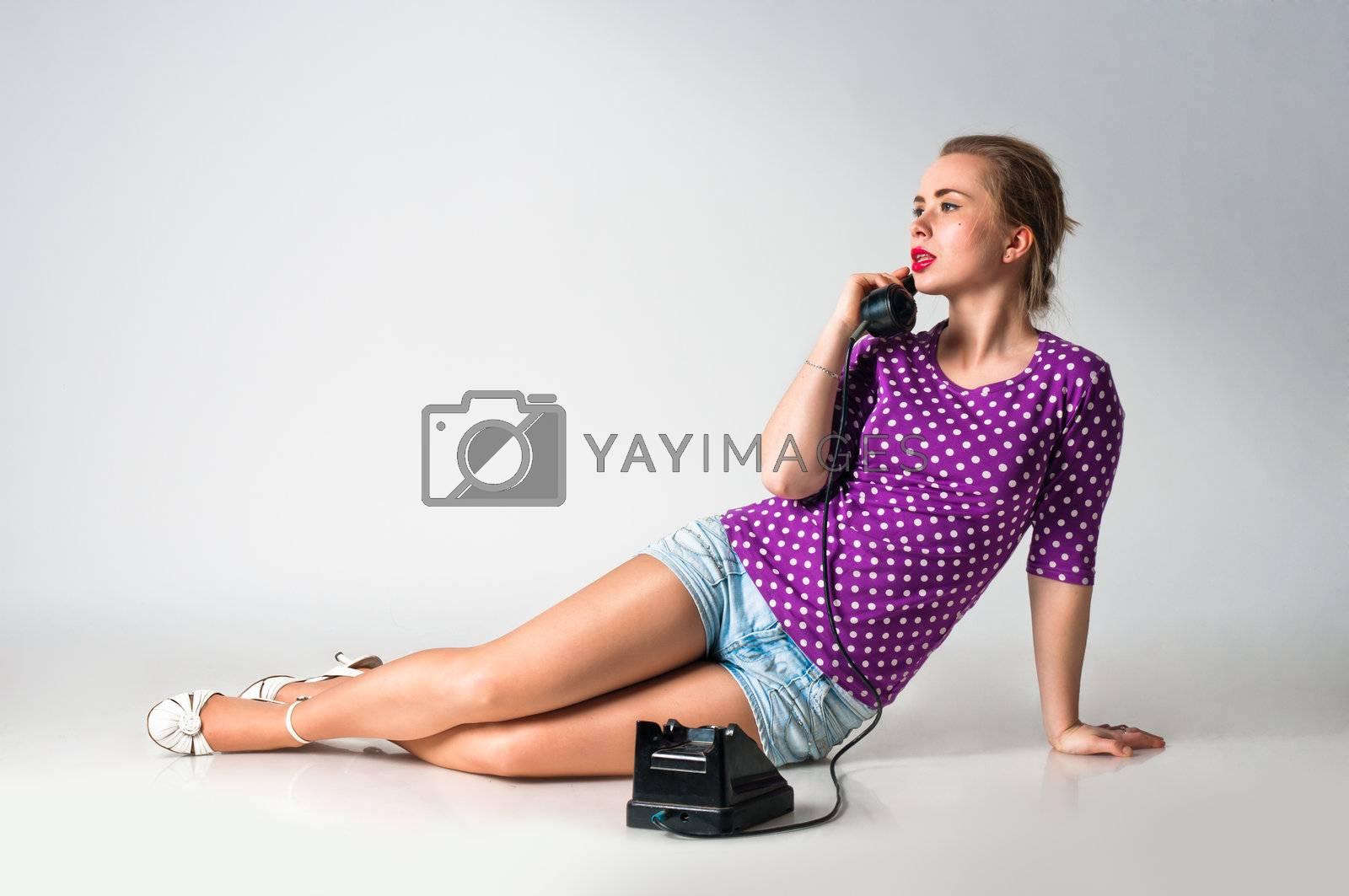 Pin up girl talking by vintage phone, studio shot
