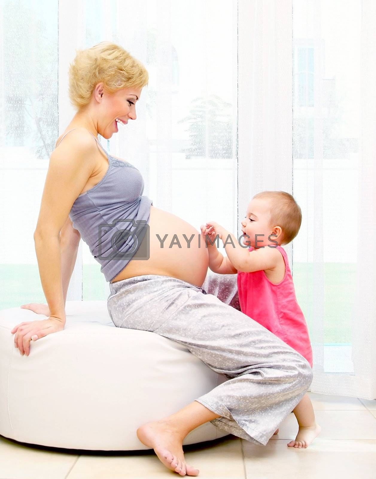 Young pregnant mother and baby girl, playing at home, happy family concept?