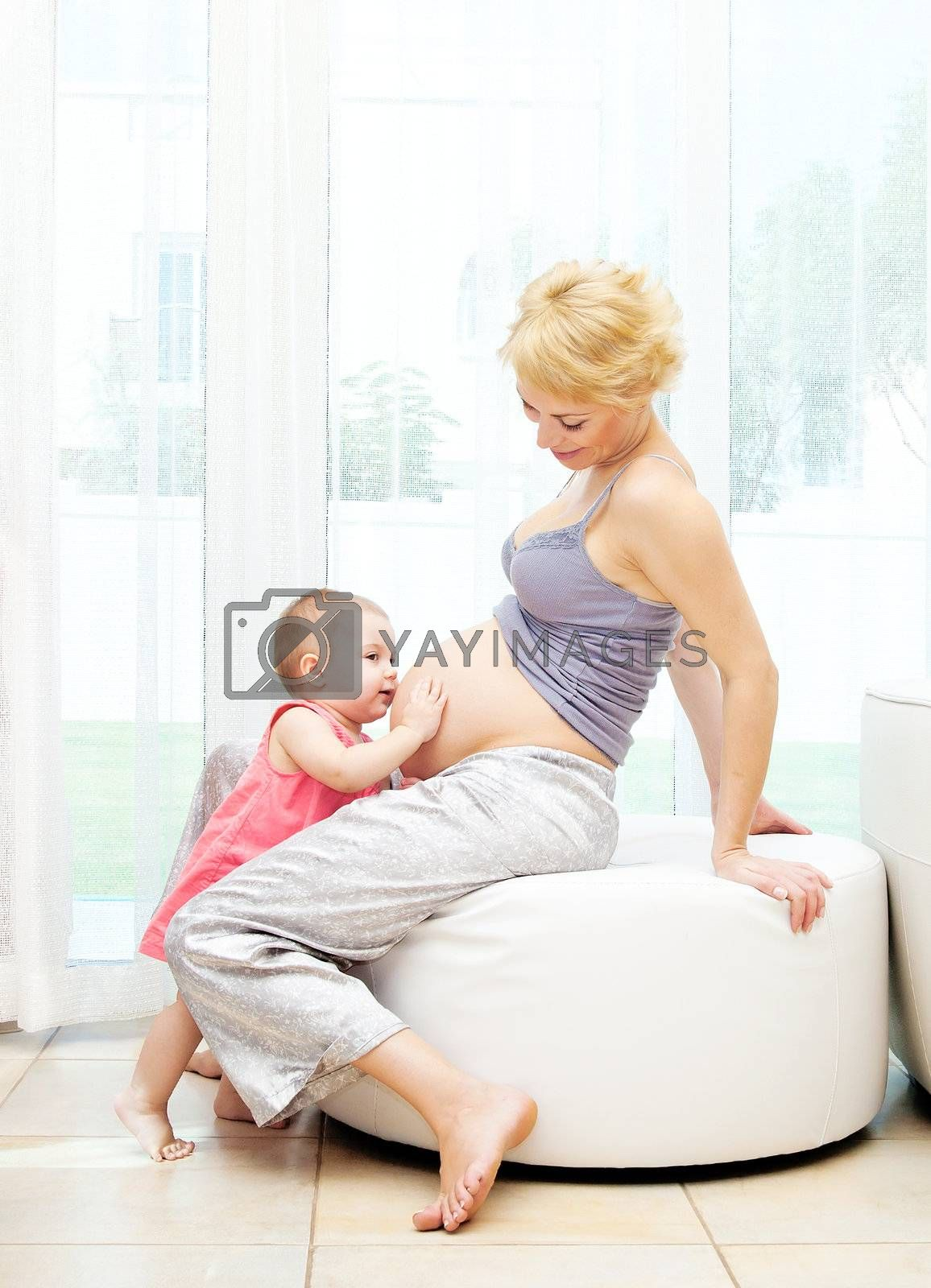 Young pregnant mother and baby girl, playing at home, happy family concept