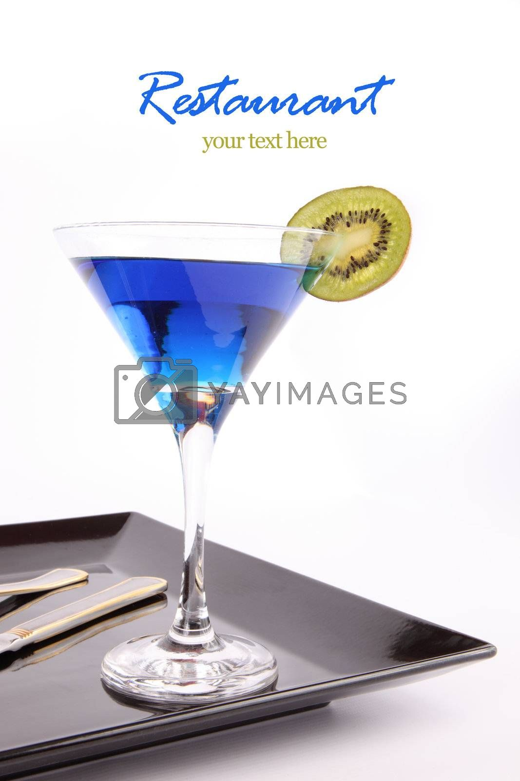 Blue drink on in a cocktail glass with Kiwi fruit in blank black dish ,  fork and knife isolated on white background with your text here