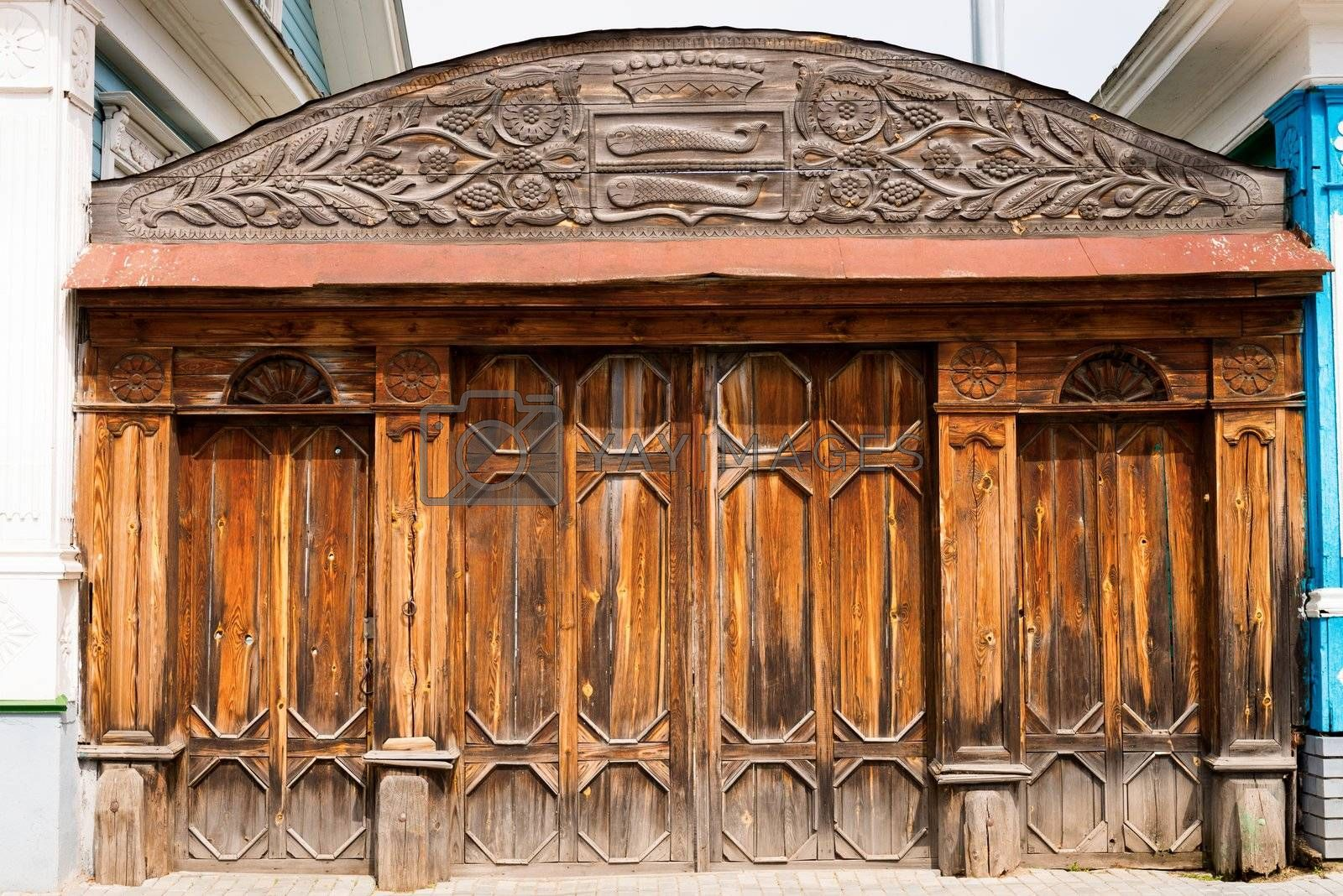 Old closed wooden ornate gate, with symbols on the top