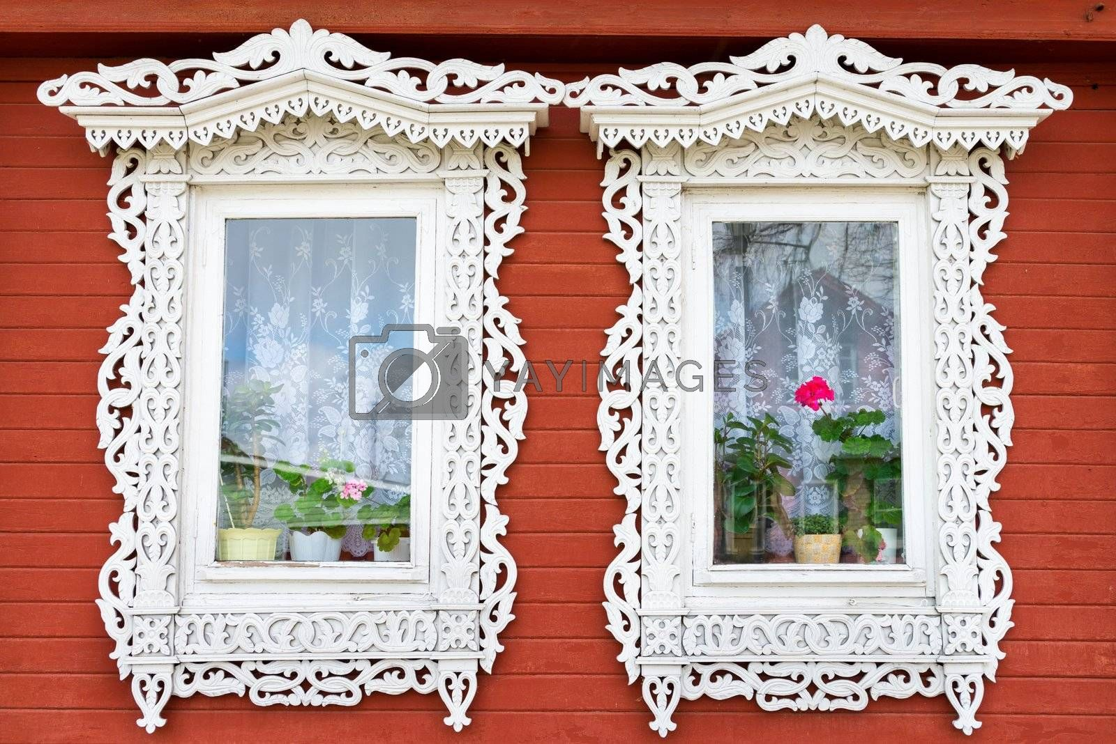 Two traditional Russian wooden window with flowers on windowsills