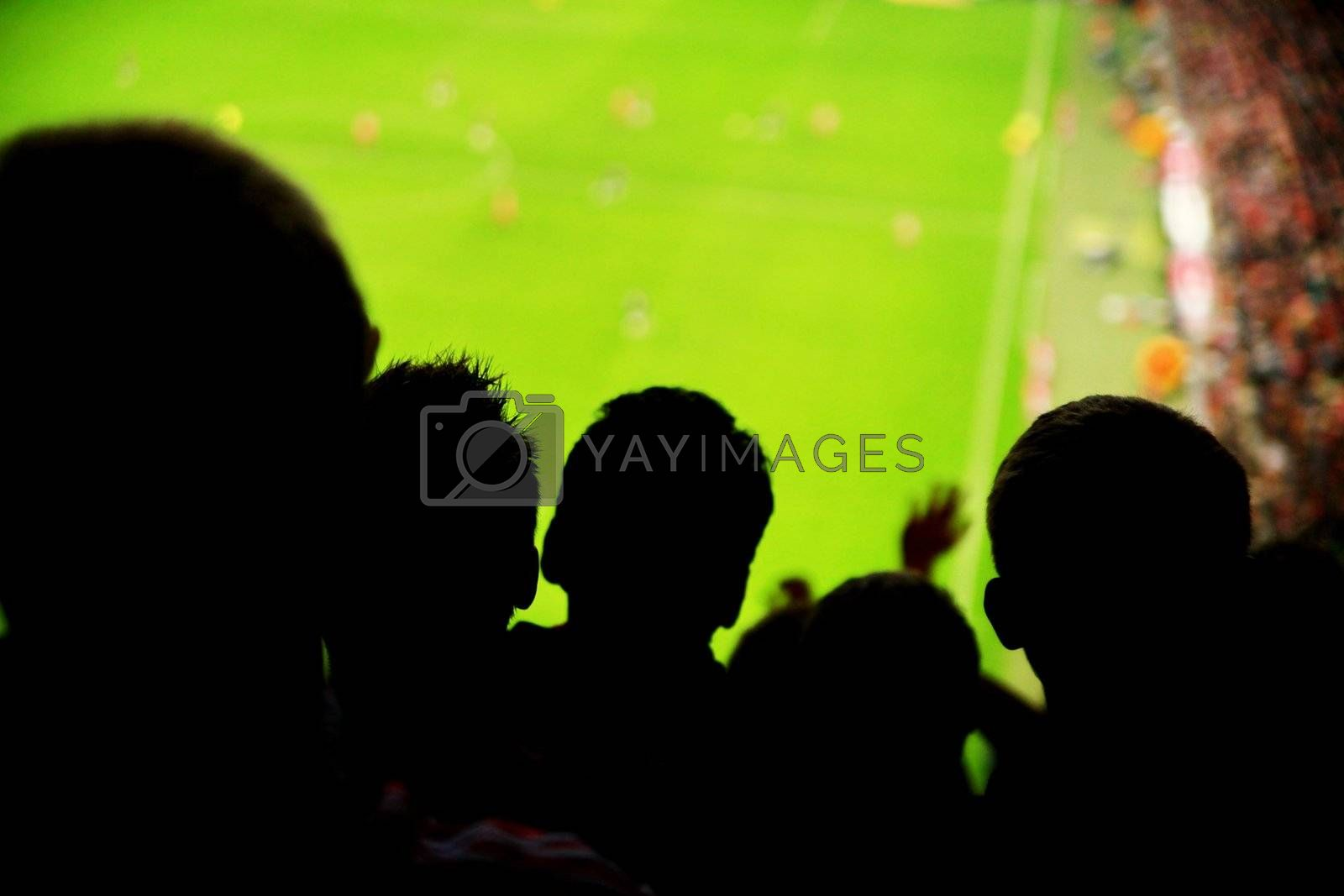 Silhouettes of fans celebrating a goal on football match