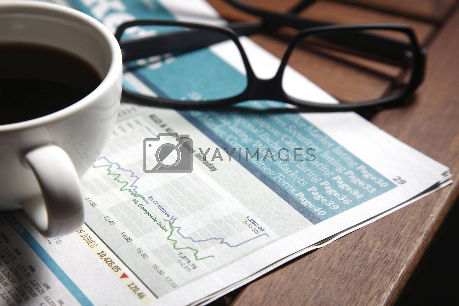 Coffee with newspapers and glasses on a table.