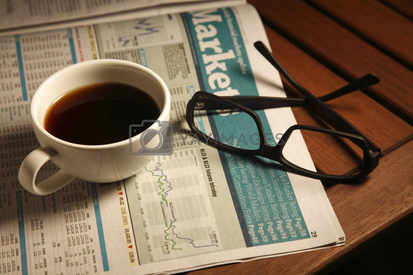 Coffee with newspaper and glasses on the table.
