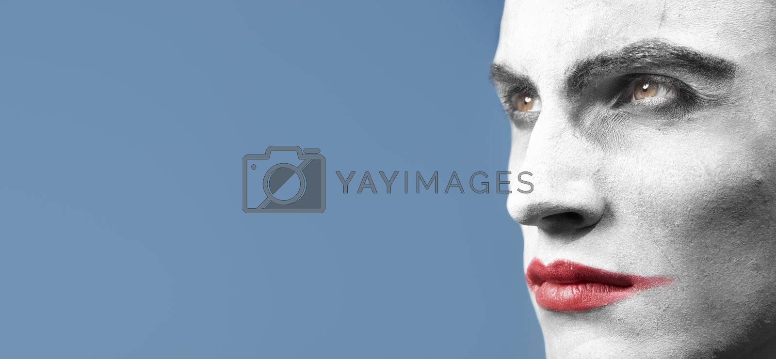 Face-painted man outdoors. Horizontal close-up photo with empty space