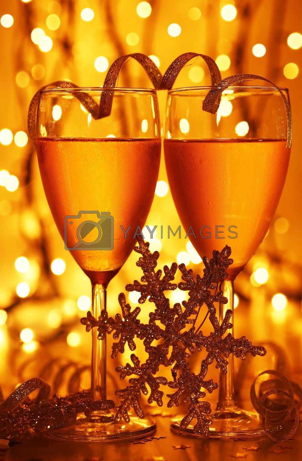 Romantic holiday dinner, celebration of Christmas or new year eve, party with Champagne and festive gold ornament decoration.