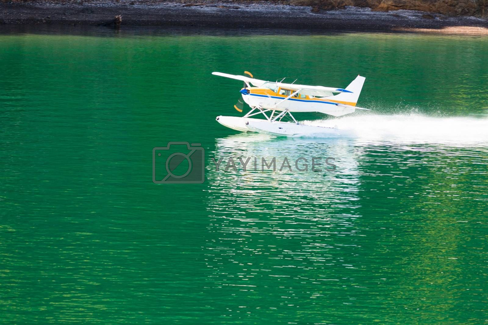 Small propeller float-plane or hydroplane takes off across flat calm water of lake