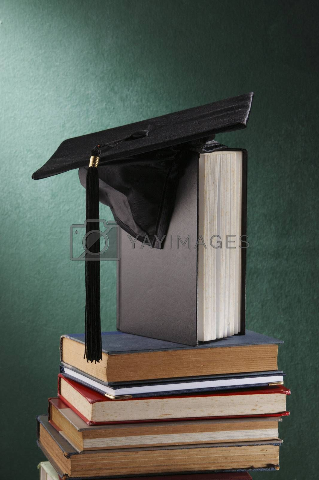 Graduation cap with book  in front of black board