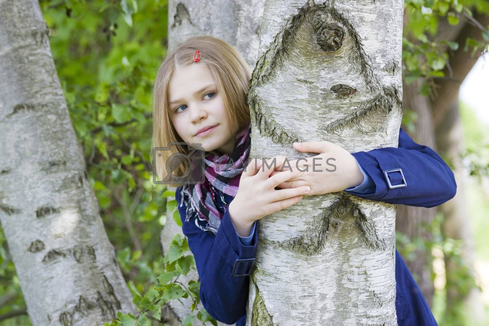 Girl hugging tree trunk and smiling