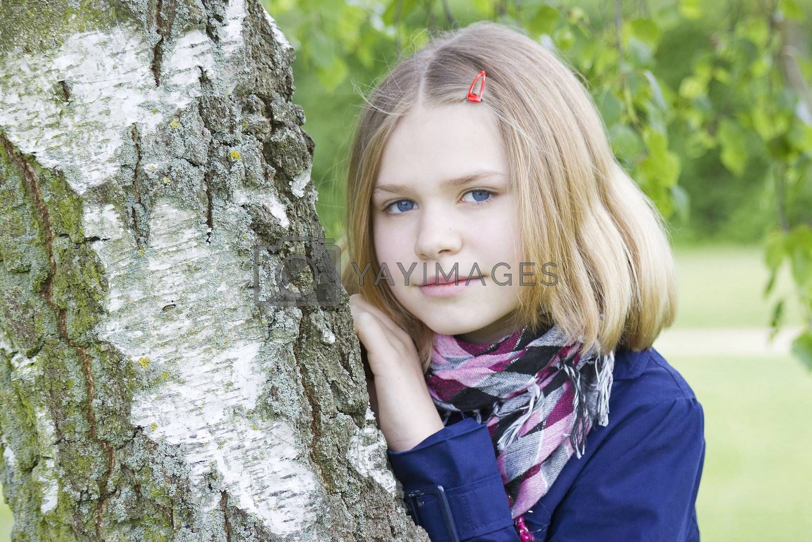 Portrait of young girl standing near birch tree at summer green park