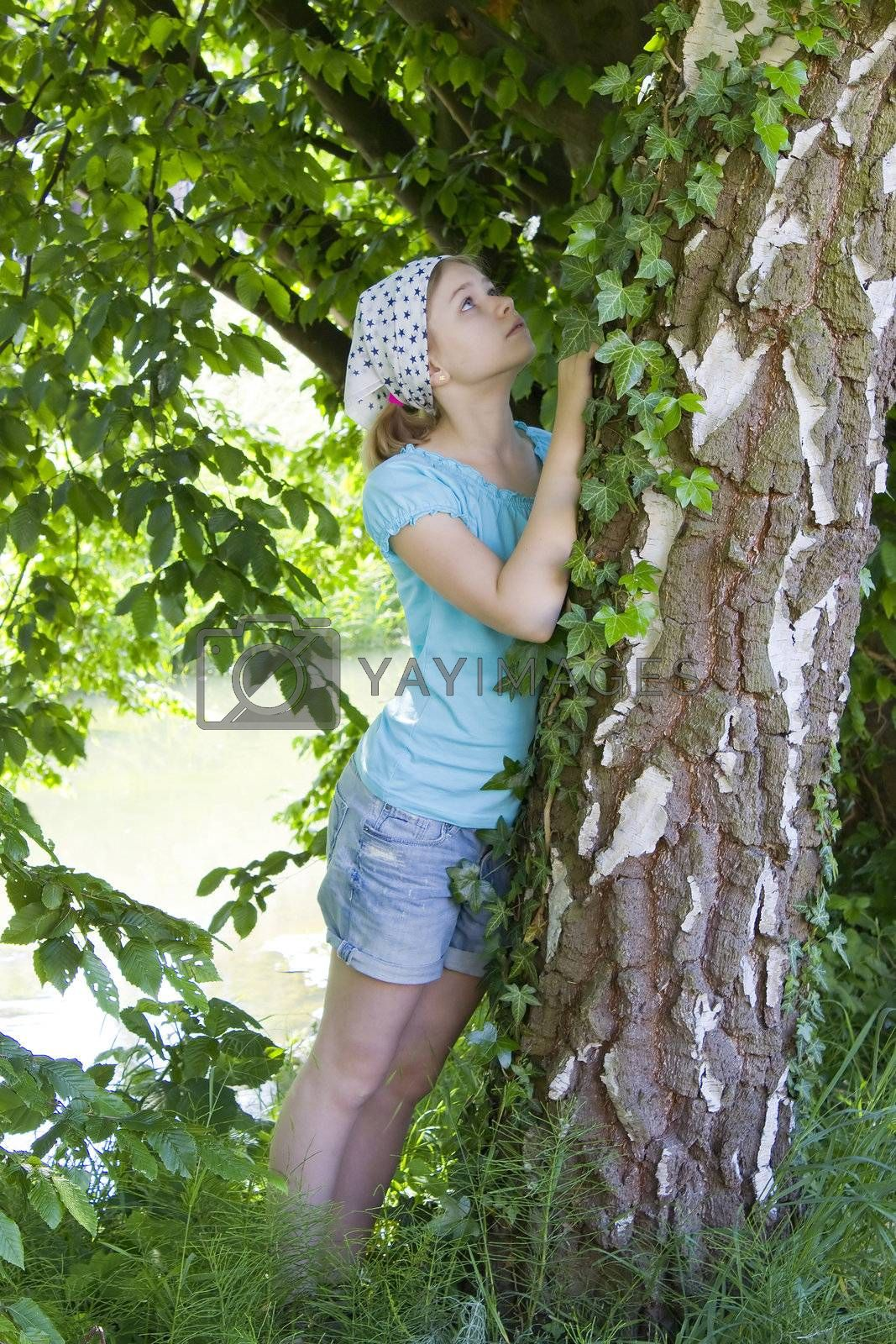 young girl standing near birch tree at summer green park