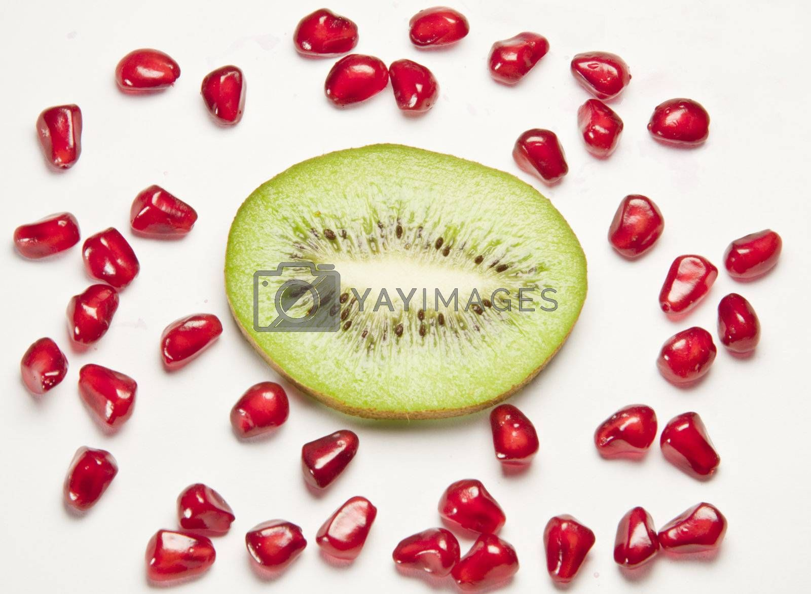 kiwi and pomegranate grains on white background