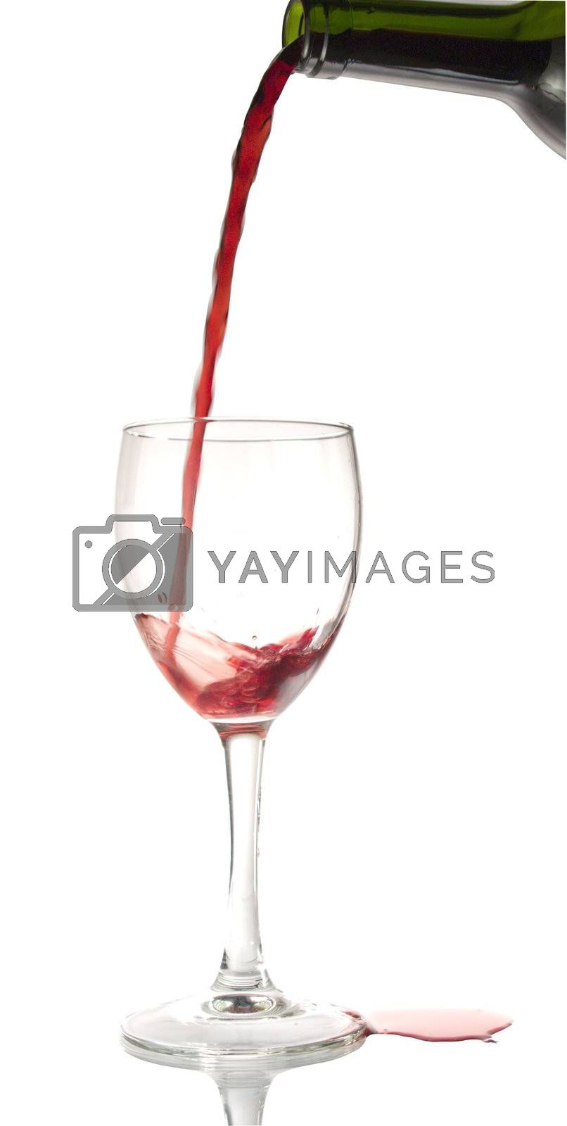Pouring red wine into a wine glass.